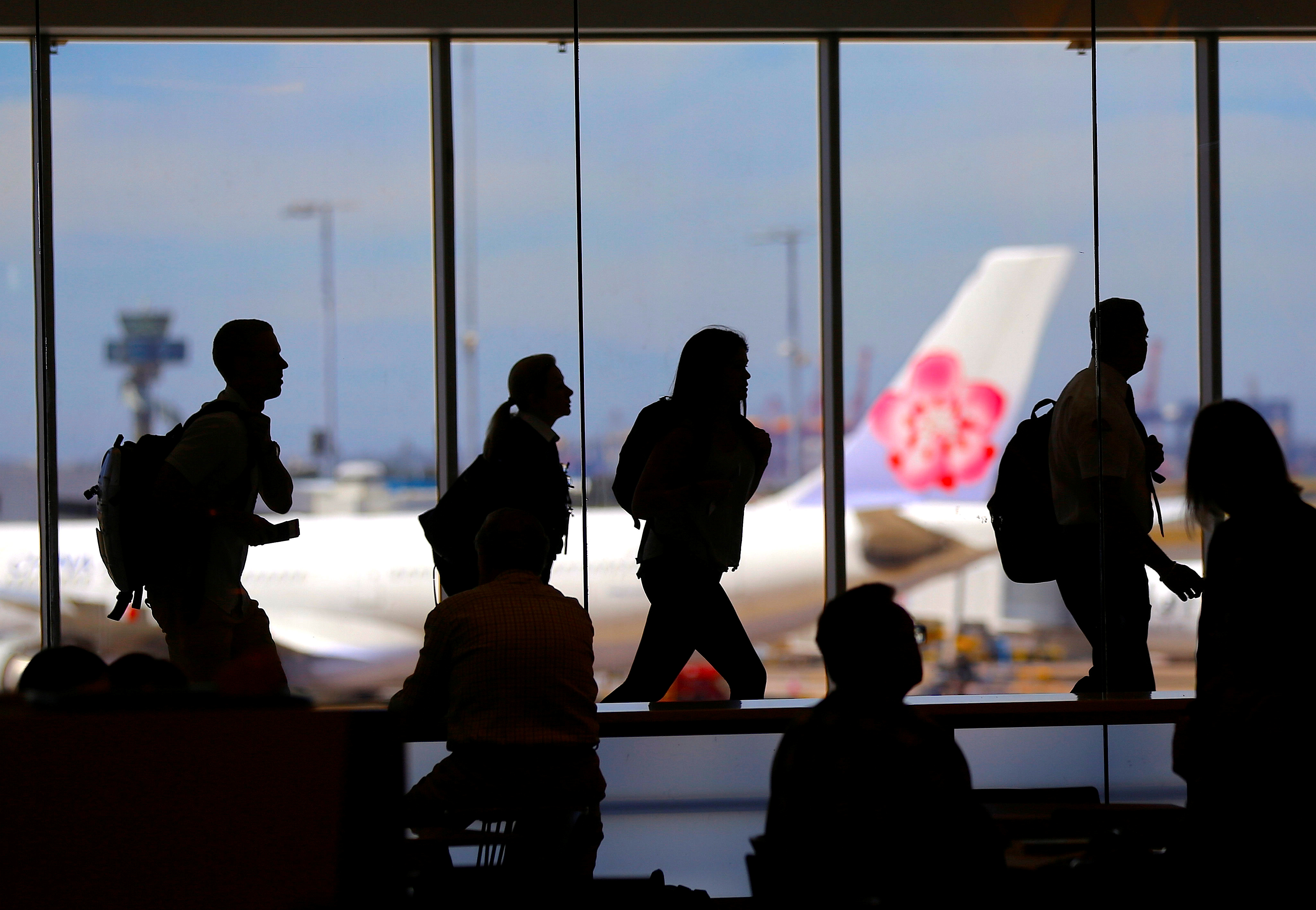Passengers walk with their luggage towards departure gates at Sydney International Airport in Australia, October 25, 2017. Picture taken October 25, 2017.     REUTERS/Steven Saphore