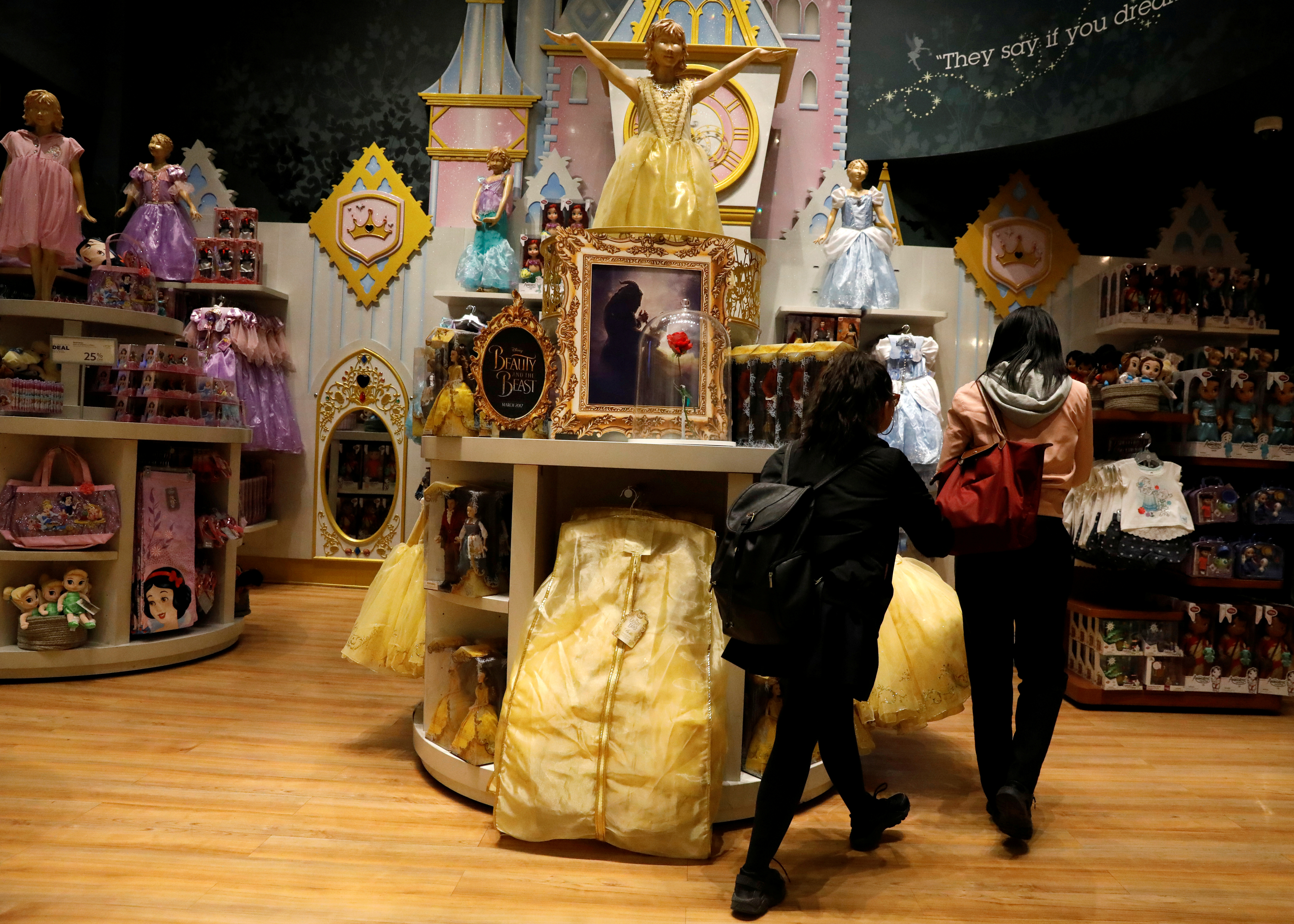 "Customers look at ""Beauty and the Beast"" merchandise in a Disney Store in New York City, U.S., May 9, 2017. REUTERS/Brendan McDermid"