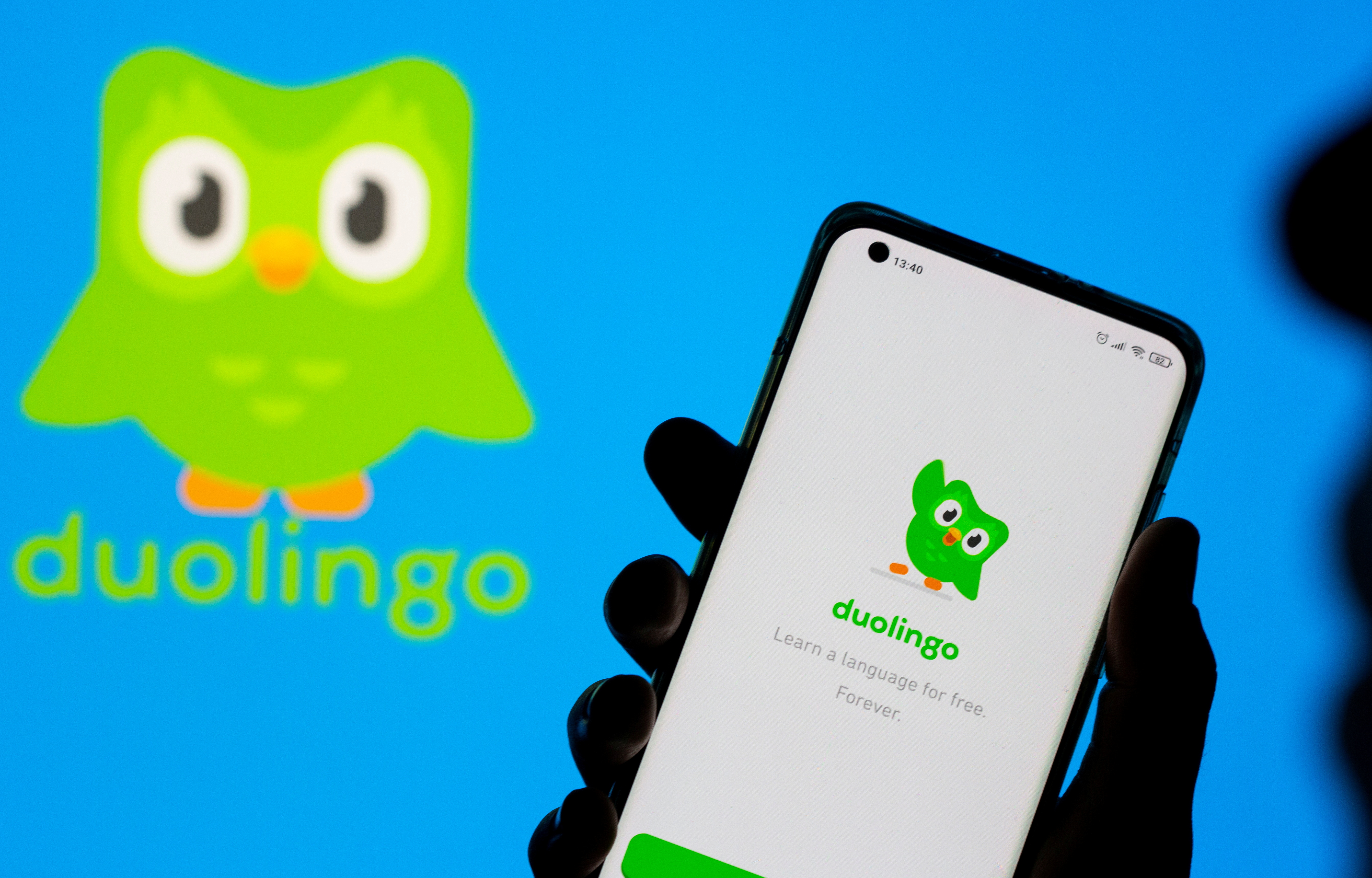 Woman with her smartphone poses in front of displayed Duolingo logo in this illustration taken, June 29, 2021. REUTERS/Dado Ruvic/Illustration/File Photo