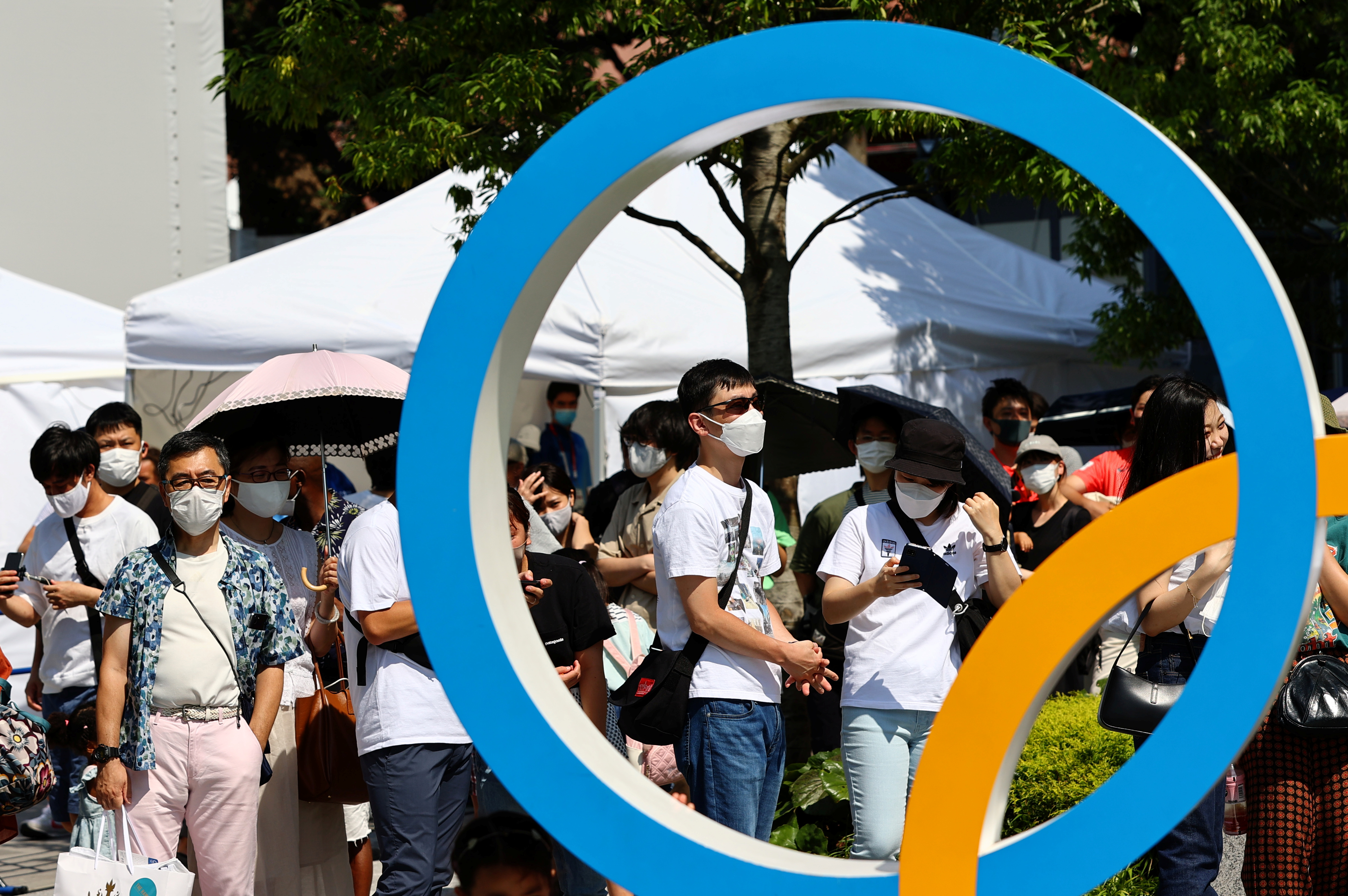 People wearing protective face masks stand in line to take a picture with an Olympic Ring outside the National Stadium, the main venue of the Tokyo 2020 Olympic Games, in Tokyo, Japan, July 24, 2021. REUTERS/Kim Kyung-Hoon