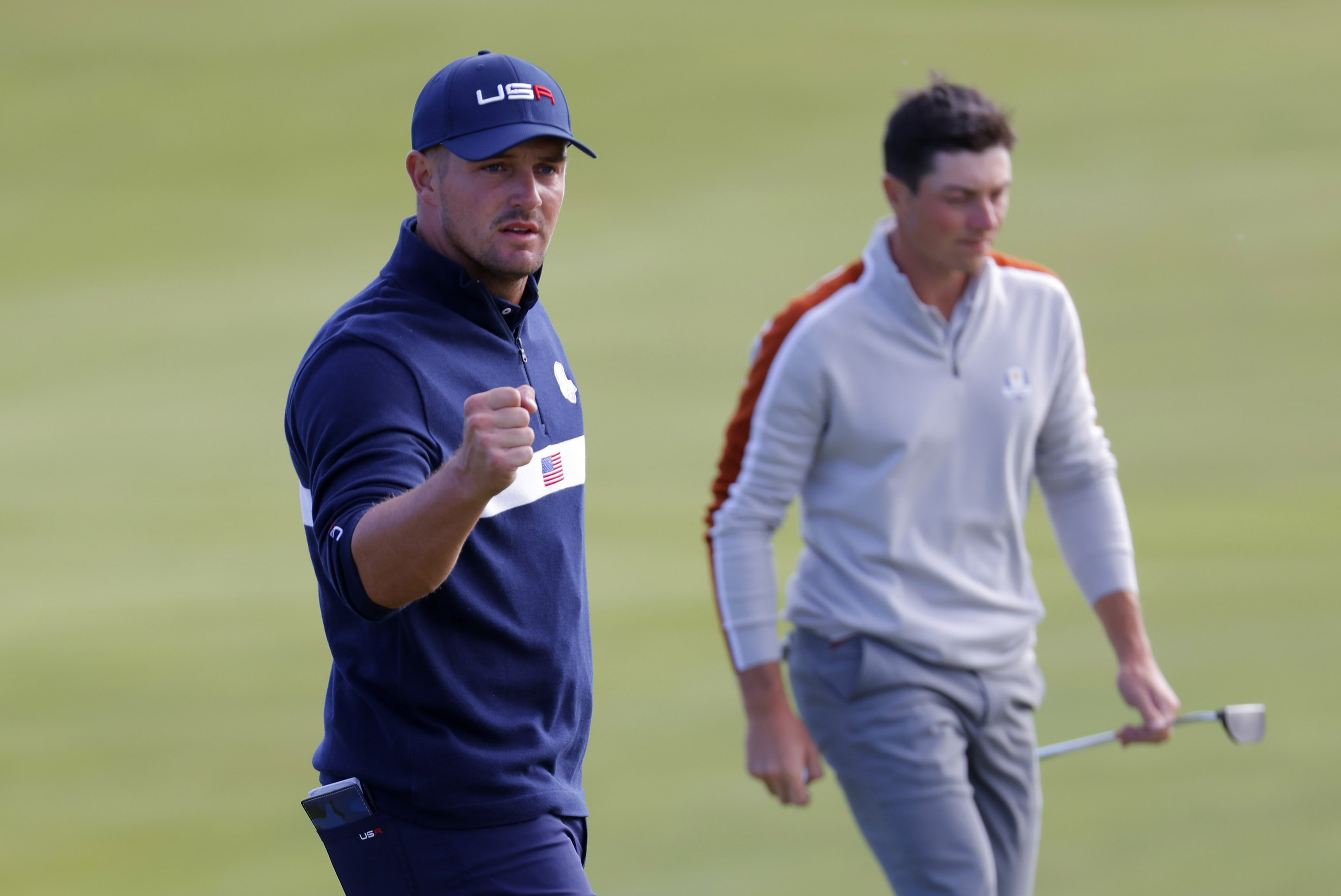 Golf - The 2020 Ryder Cup - Whistling Straits, Sheboygan, Wisconsin, U.S. - September 25, 2021 Team USA's Bryson DeChambeau reacts after holing his putt on the 10th green as Team Europe's Viktor Hovland looks on during the Four-balls REUTERS/Mike Segar