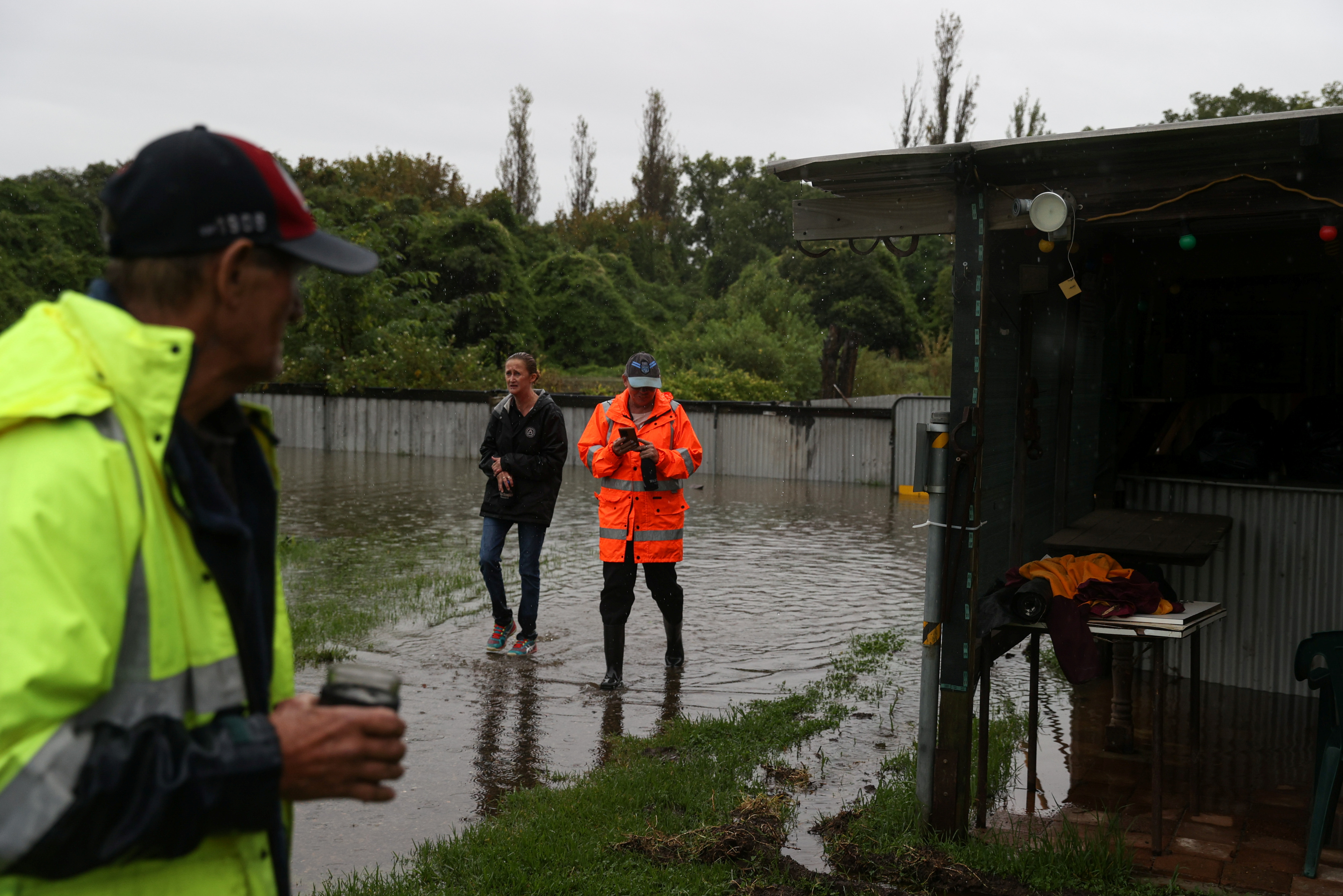 Local residents walk through their property to check on a house while floodwaters rise in the suburb of Riverstone, as the state of New South Wales experiences widespread flooding and severe weather, in Sydney, Australia, March 22, 2021.  REUTERS/Loren Elliott
