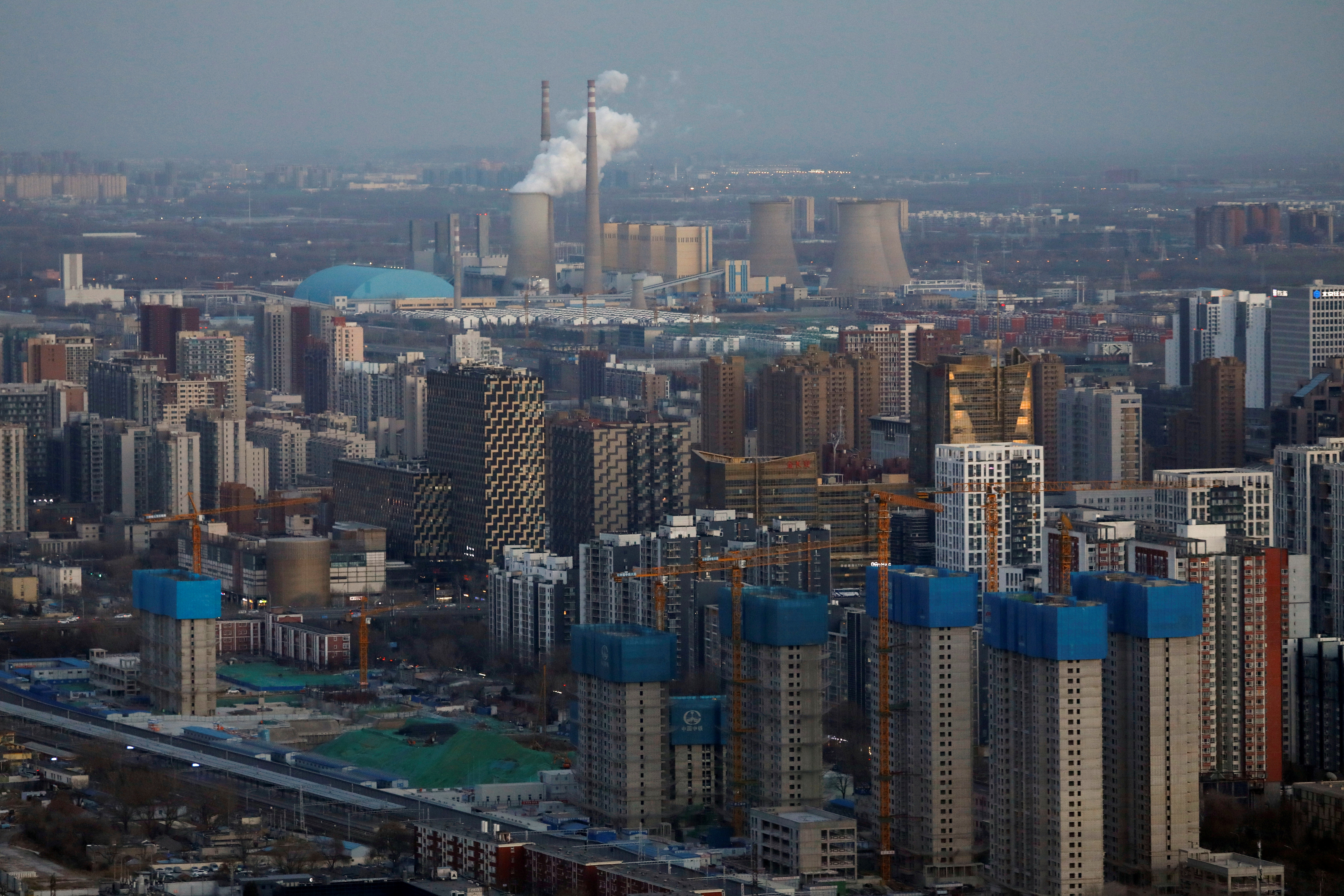Residential buildings under construction and a power station are seen near the central business district (CBD) in Beijing, China, January 15, 2021. REUTERS/Tingshu Wang/File Photo