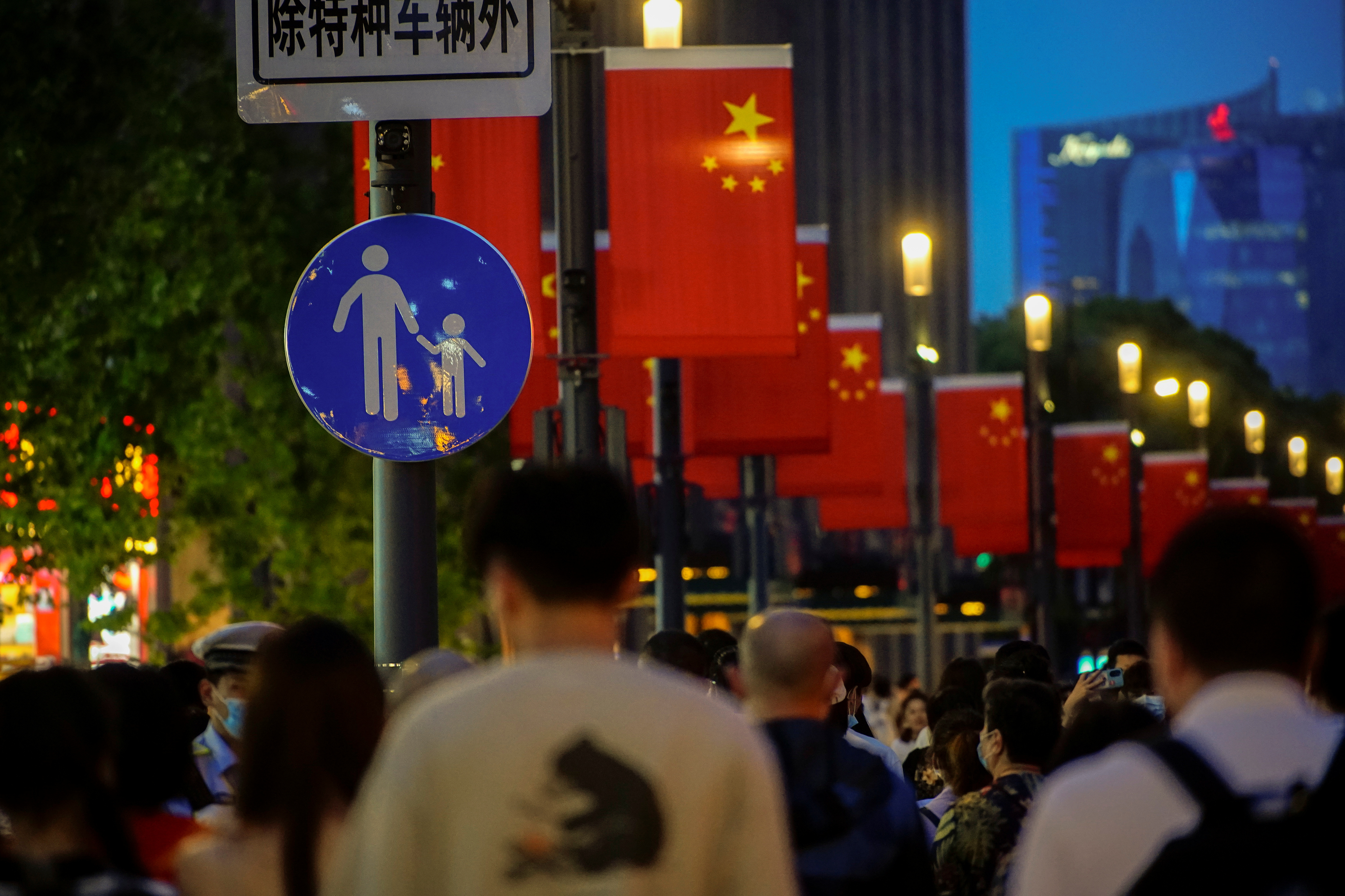 People walk along Nanjing Pedestrian Road, a main shopping area, following the outbreak of the coronavirus disease (COVID-19), in Shanghai, China May 10, 2021. REUTERS/Aly Song/Files