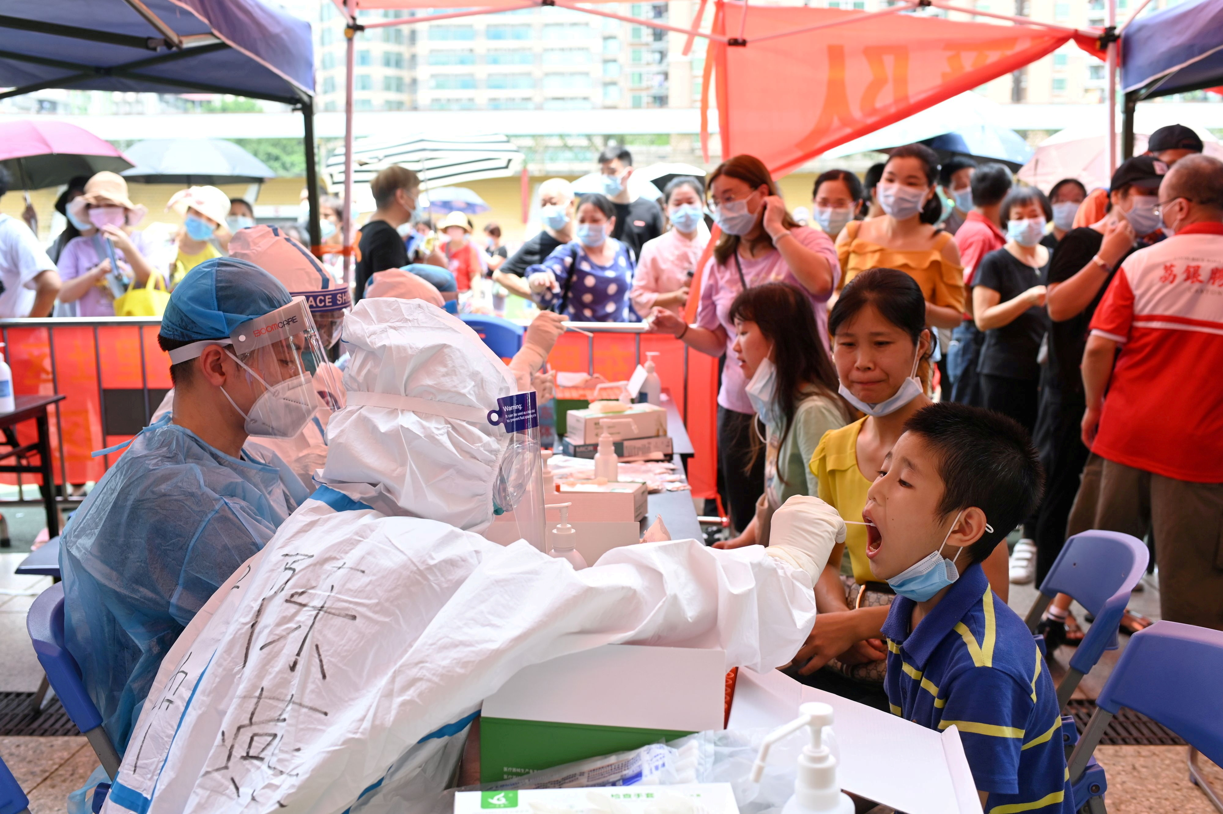 A medical worker collects a swab from a resident during a mass testing for the coronavirus disease (COVID-19) at a makeshift testing site at a stadium in Guangzhou, Guangdong province, China May 30, 2021. cnsphoto via REUTERS