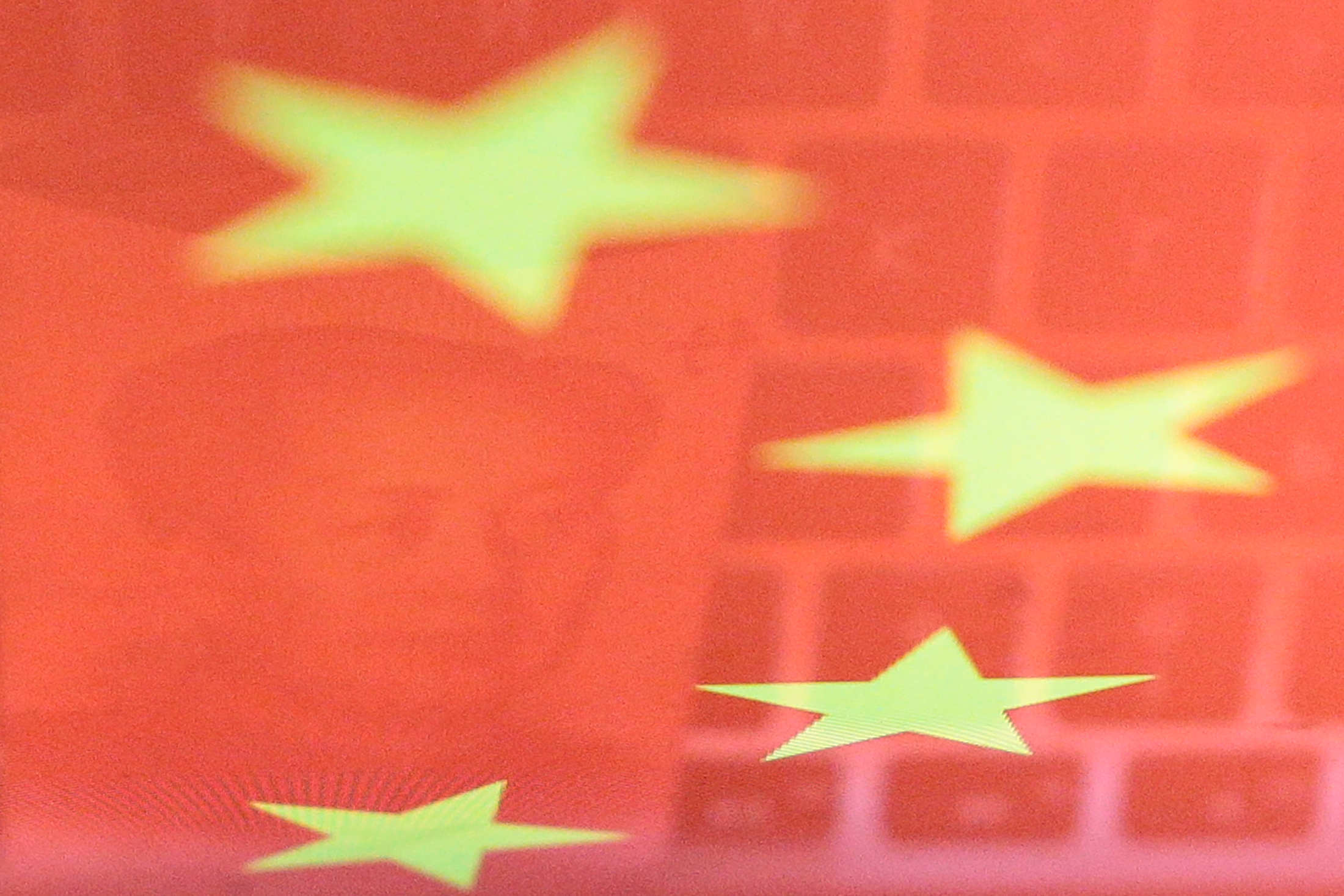 A China yuan banknote featuring late Chinese chairman Mao Zedong and a computer keyboard are seen reflected on an image of Chinese flag in this illustration picture.  REUTERS/Florence Lo/Illustration