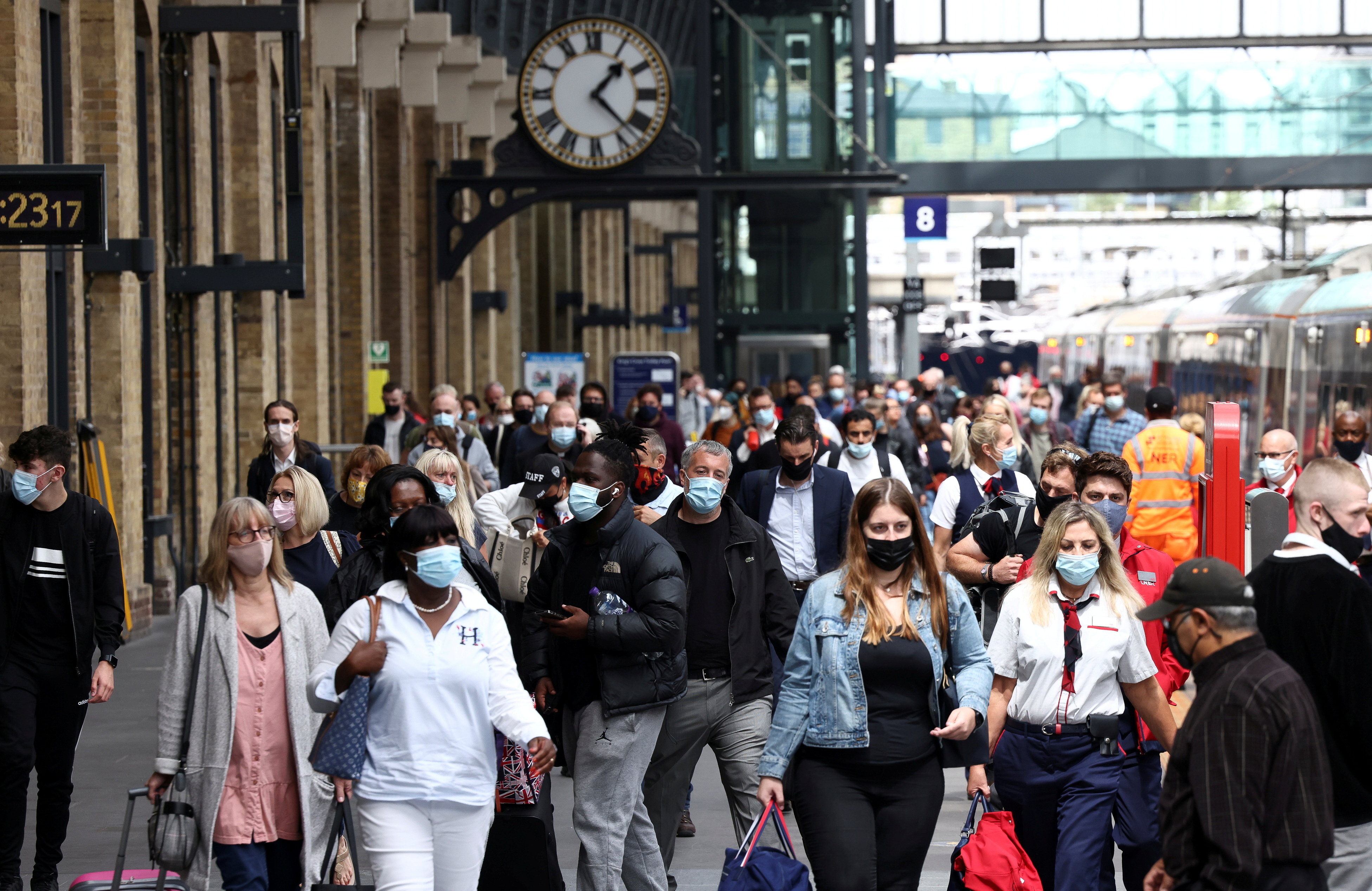 People wearing protective face masks walk along a platform at King's Cross Station, amid the coronavirus disease (COVID-19) outbreak in London, Britain, July 12, 2021. REUTERS/Henry Nicholls/File Photo