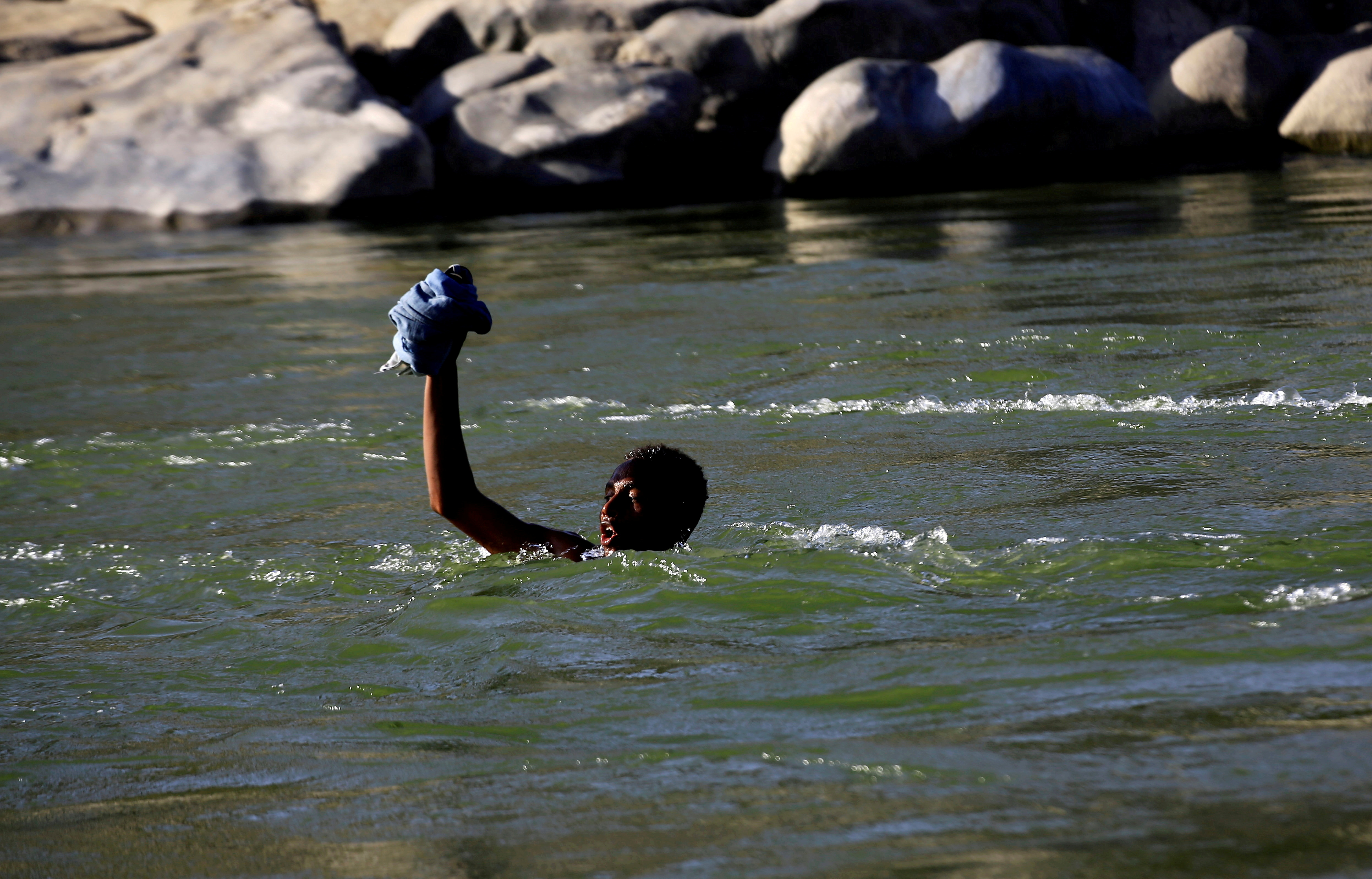 An Ethiopian fleeing fighting in Tigray region lifts his clothes as he crosses the Setit river on the Sudan-Ethiopia border in Hamdayet village in eastern Kassala state, Sudan November 22, 2020. REUTERS/Mohamed Nureldin Abdallah//File Photo