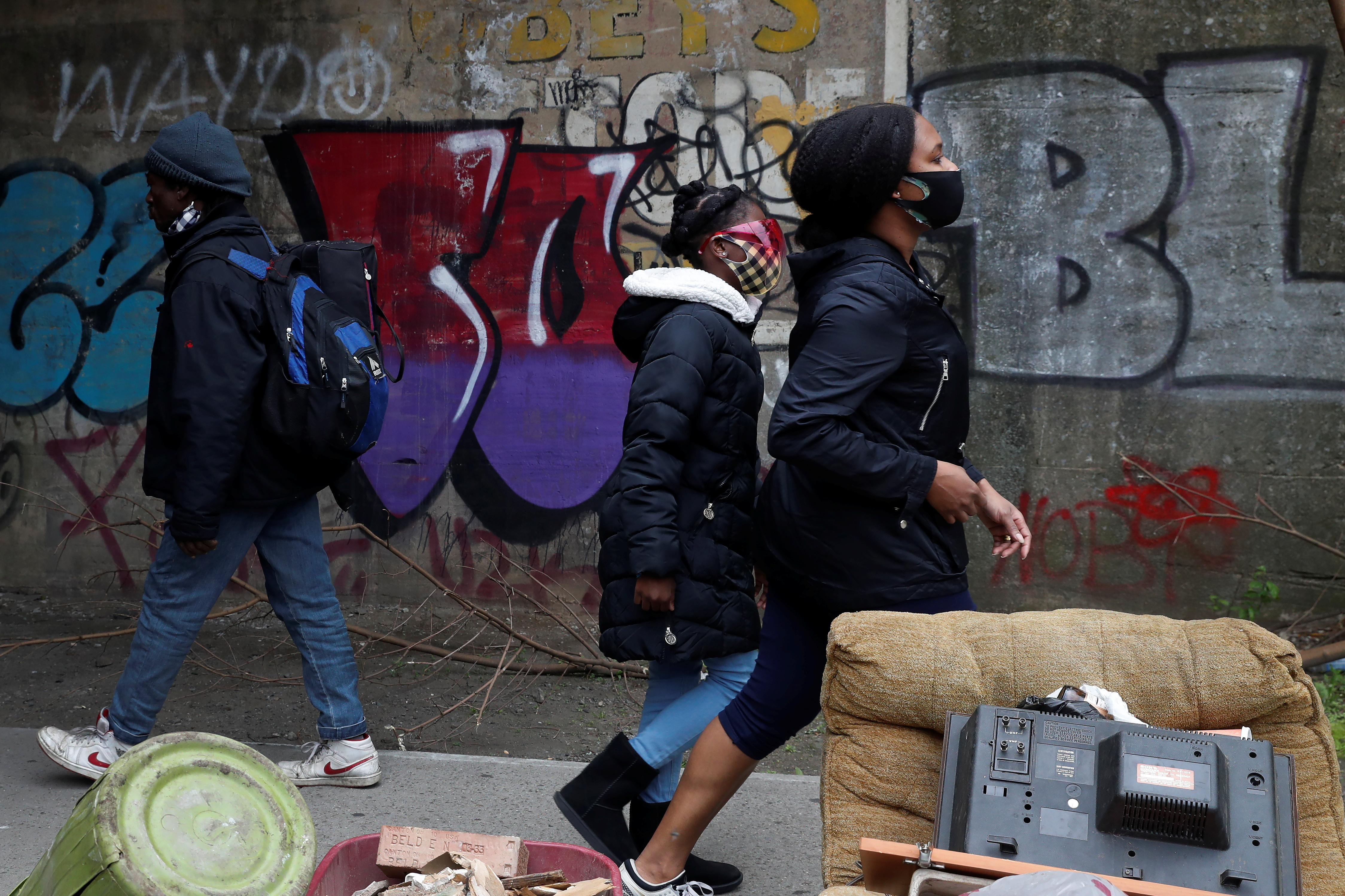 People wearing protective masks walk by a man not wearing a mask over his nose under the subway in the Brownsville section of the Brooklyn borough of New York City, U.S., May 3, 2021. REUTERS/Shannon Stapleton