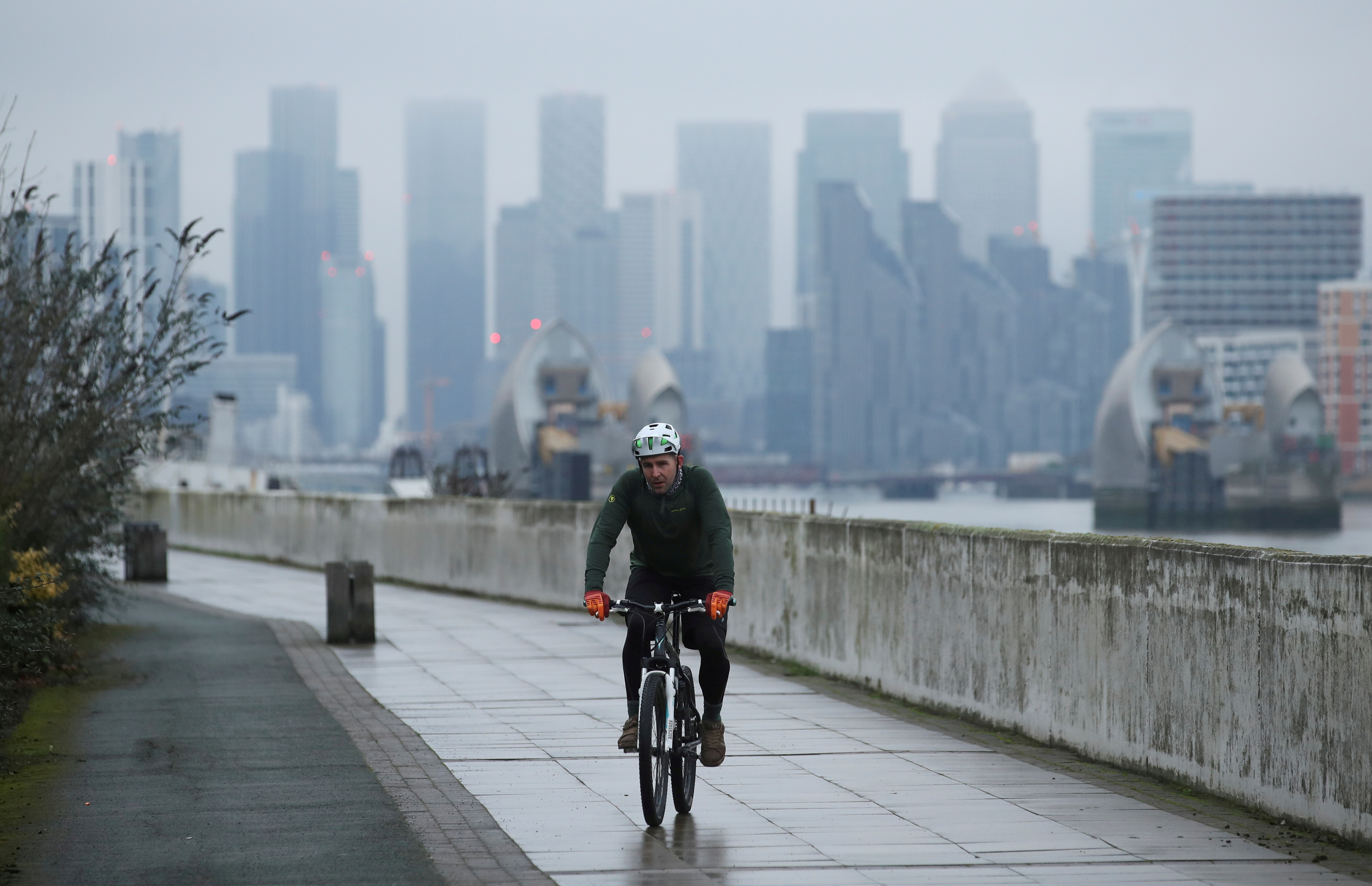 Buildings are seen in the Canary Wharf business district, as a man cycles along a path, in London, Britain January 27, 2021. REUTERS/Peter Cziborra