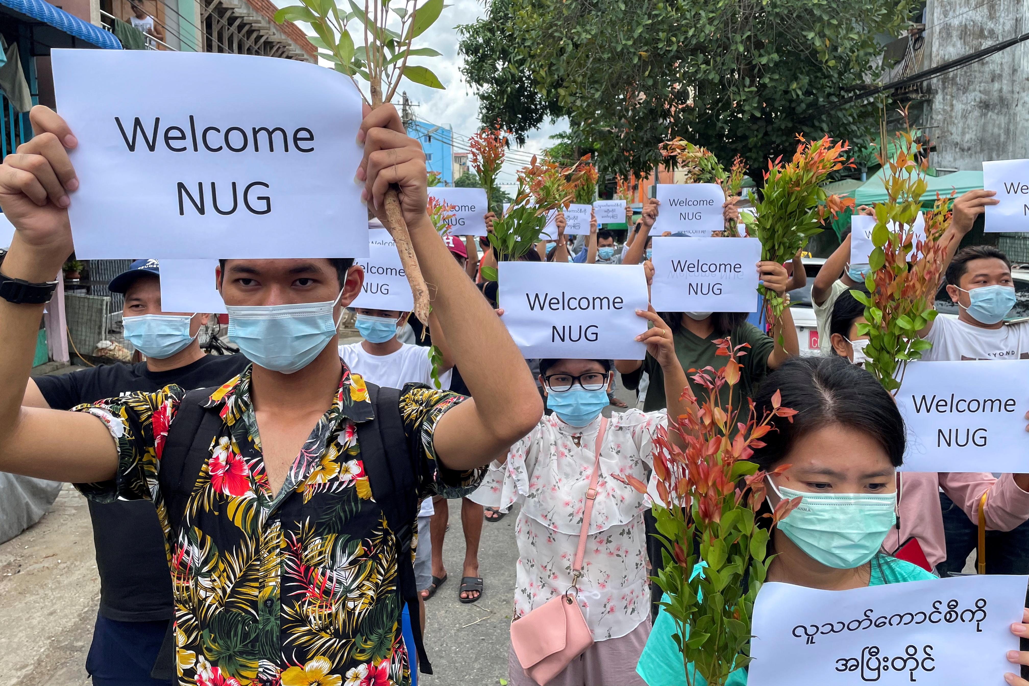 Pengunjuk rasa anti-pemerintah memegang plakat untuk menunjukkan dukungan mereka dan menyambut Pemerintah Persatuan Nasional baru yang didirikan oleh legislator NLD yang digulingkan dan menyerukan untuk melanjutkan pemogokan dari tahun baru tradisional di Myanmar, di Yangon, Myanmar, 17 April 2021. REUTERS / Stringer /