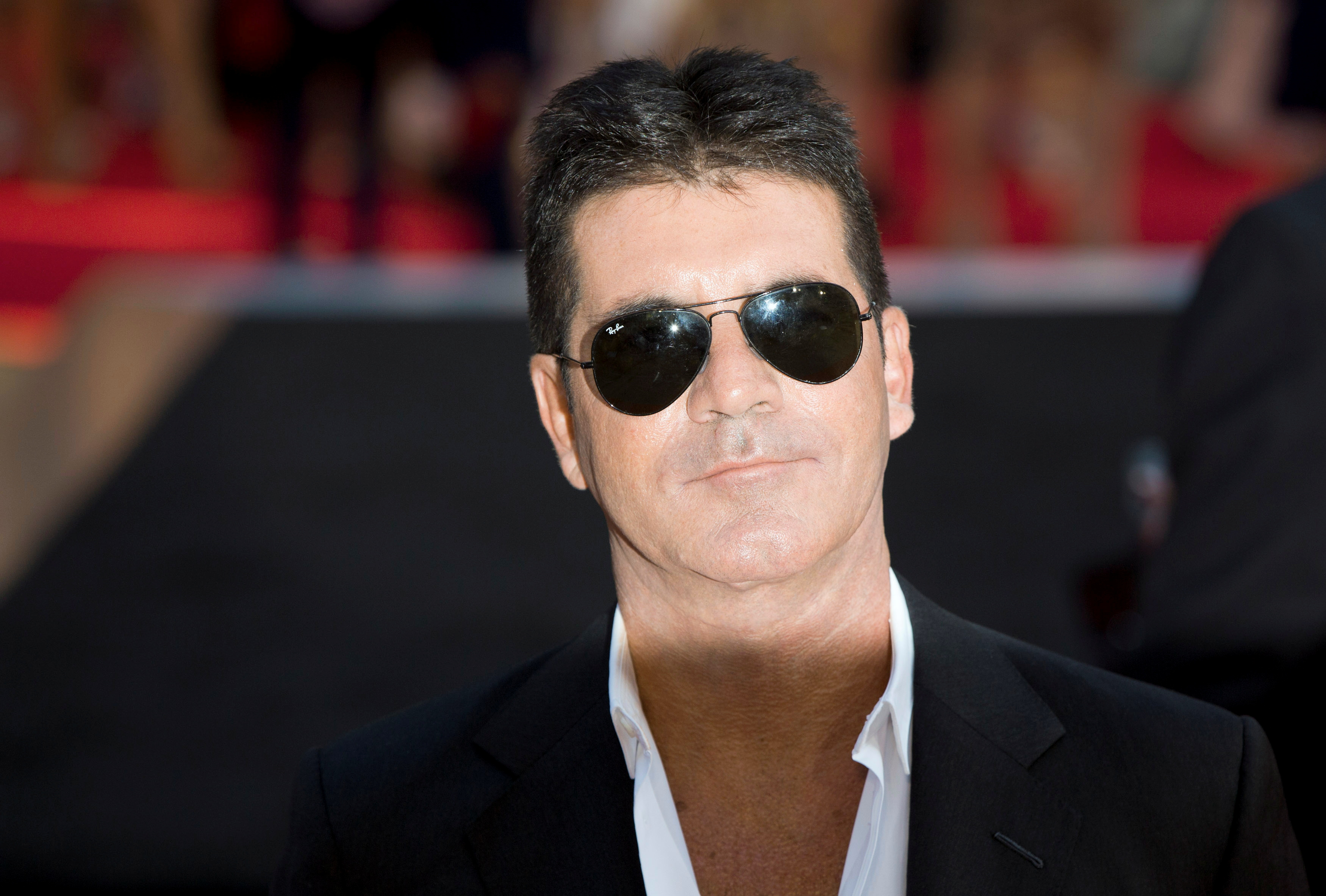Television mogul Simon Cowell poses for photographers as he arrives for the film