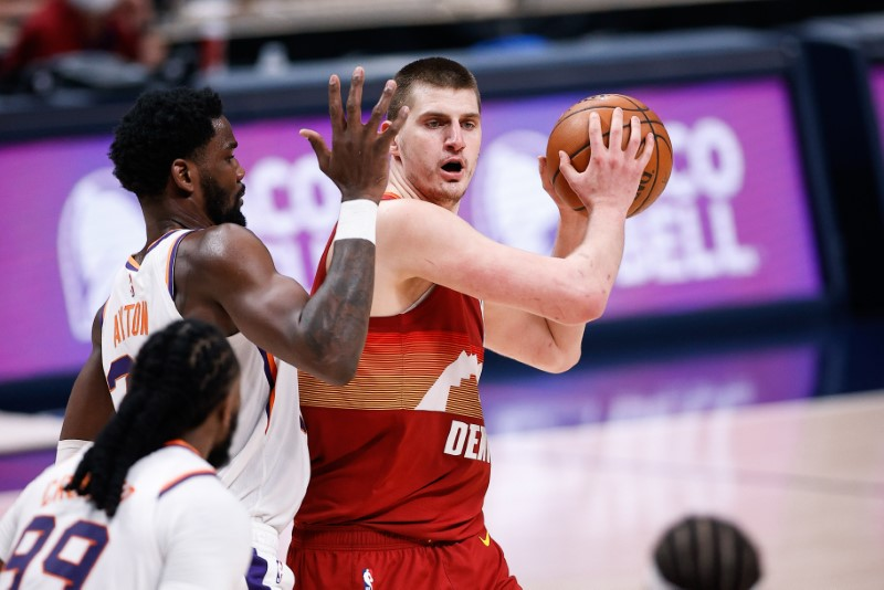 Jun 13, 2021; Denver, Colorado, USA; Denver Nuggets center Nikola Jokic (15) controls the ball as Phoenix Suns center Deandre Ayton (22) defends in the third quarter during game four in the second round of the 2021 NBA Playoffs at Ball Arena. Mandatory Credit: Isaiah J. Downing-USA TODAY Sports