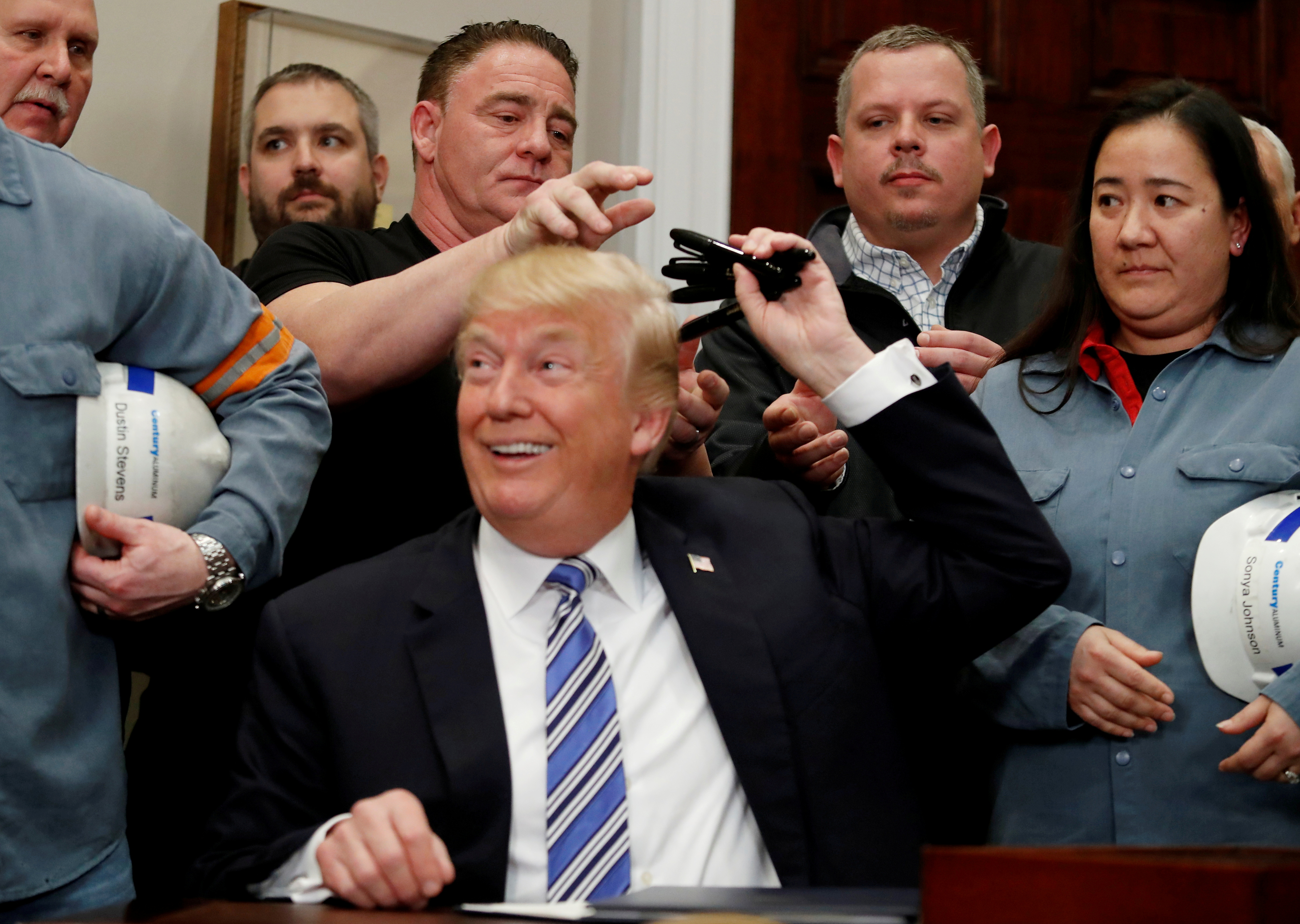 U.S. President Donald Trump gives out pens he used to sign presidential proclamations placing tariffs on steel and aluminum imports to workers from the steel and aluminum industries at the White House in Washington, U.S. March 8, 2018. REUTERS/Leah Millis