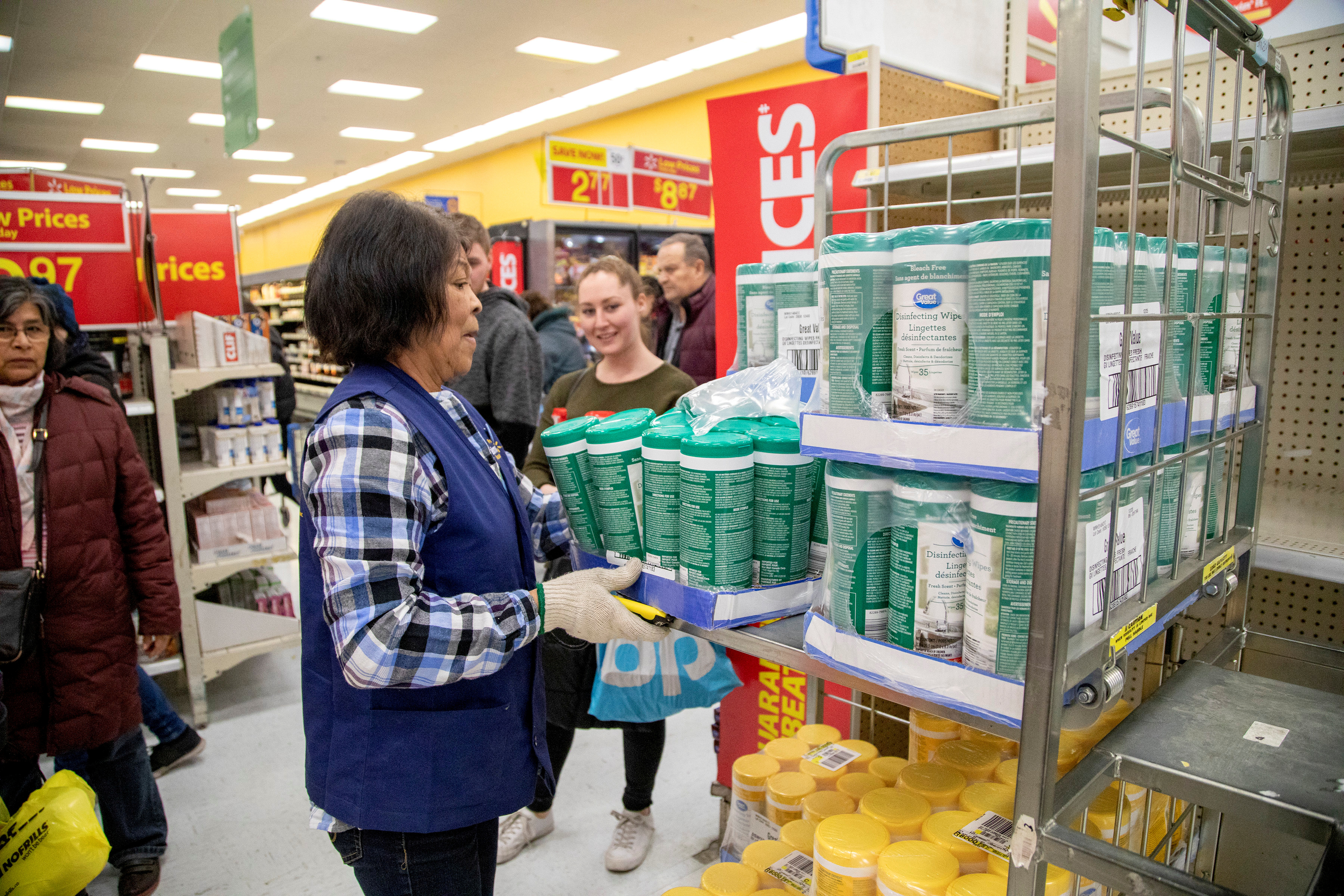 People wait as an employee restocks a shelf with disinfectant wipes as people shop at a Walmart Supercentre amid coronavirus fears spreading in Toronto, Ontario, Canada March 13, 2020.  REUTERS/Carlos Osorio/File Photo
