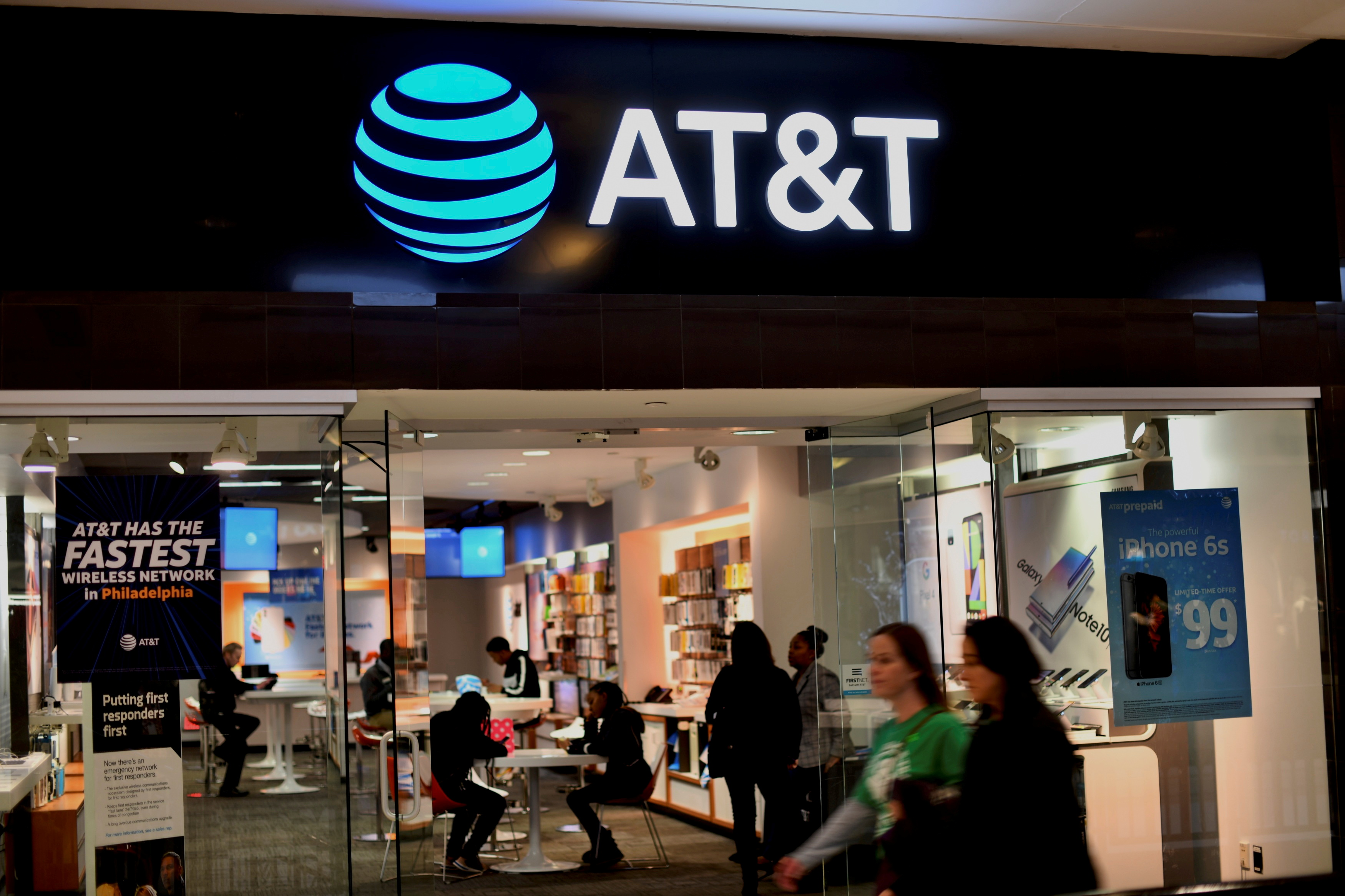 Shoppers walk past an AT&T store at the King of Prussia Mall in King of Prussia, Pennsylvania, U.S. November 22, 2019. REUTERS/Mark Makela/File Photo