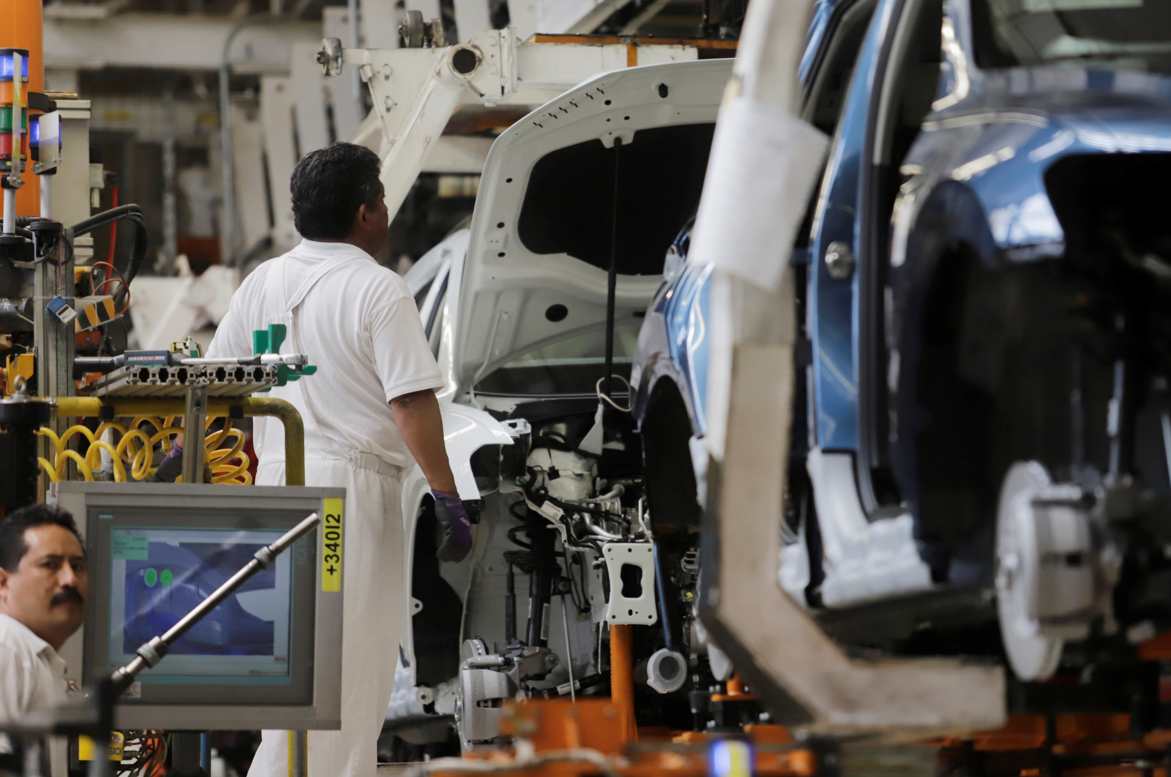 An employee works on the production line of the Volkswagen Tiguan cars at the company's assembly plant in Puebla, Mexico, July 10, 2019. Picture taken on July 10, 2019.  REUTERS/Imelda Medina/Files