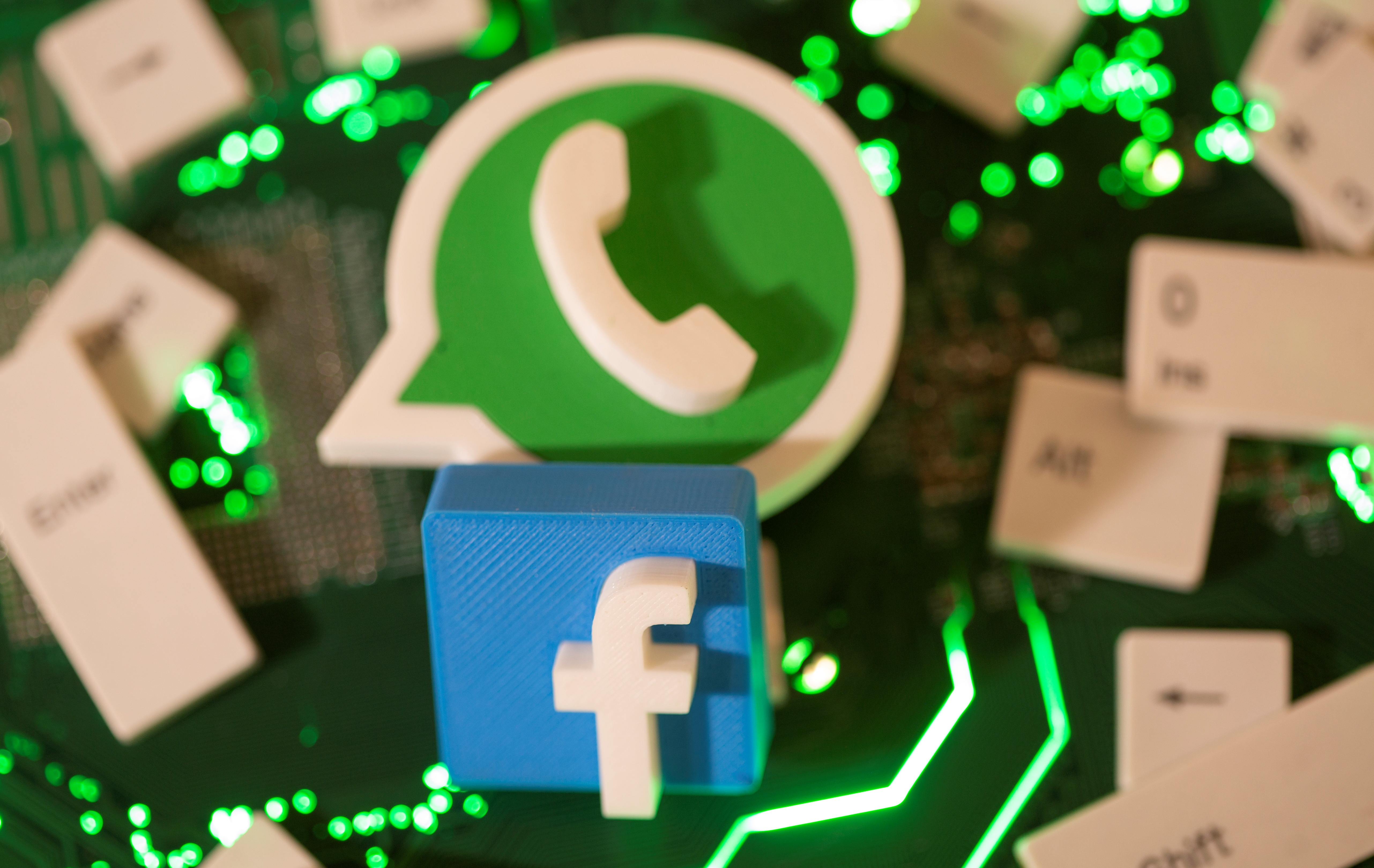 3D printed Facebook and WhatsApp logos and keyboard buttons are placed on a computer motherboard in this illustration taken January 21, 2021. REUTERS/Dado Ruvic/File Photo