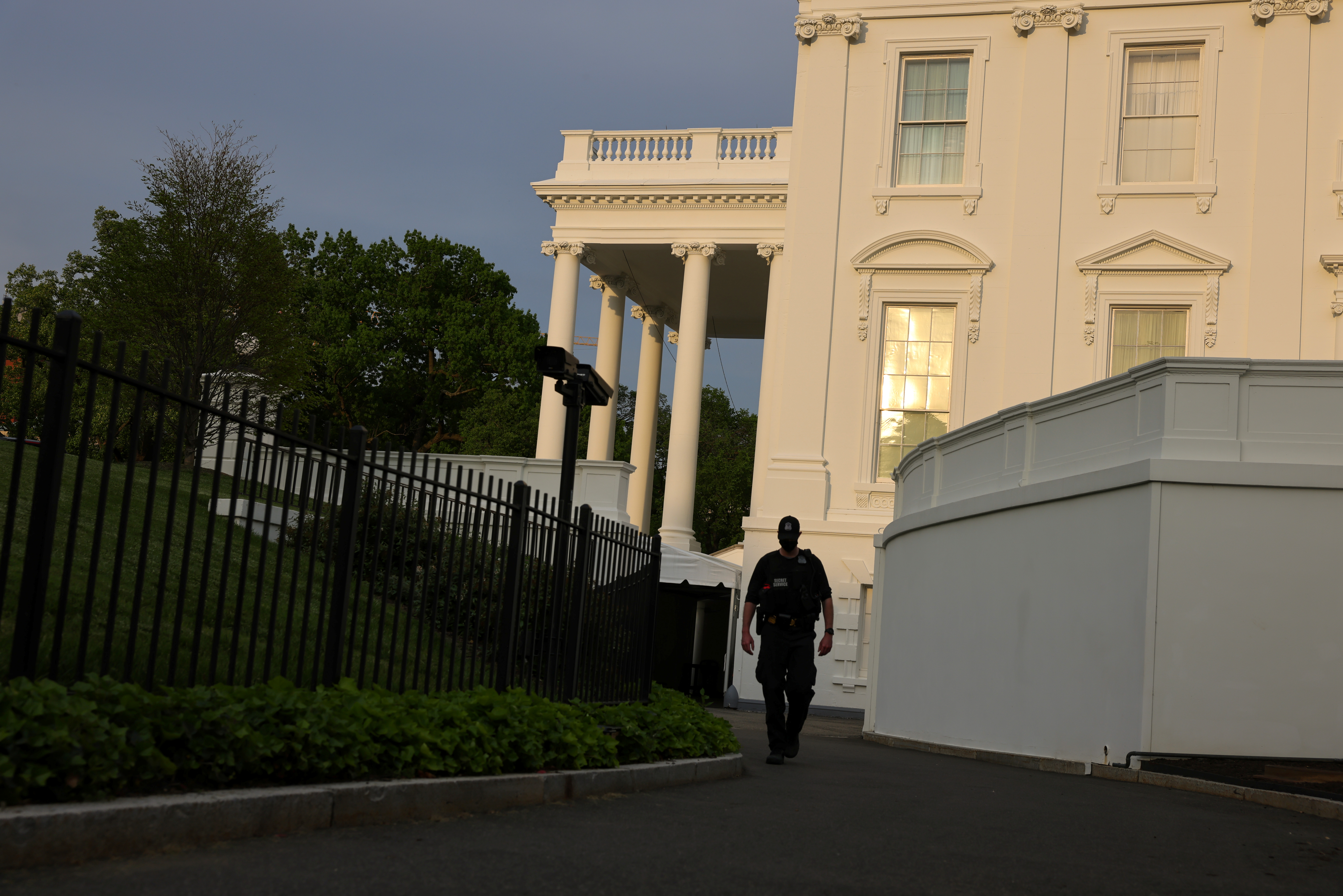 The sun reflects off the White House as a secret service agent walks past prior to President Joe Biden's speech before the Joint Session of Congress in Washington, U.S., April 28, 2021. REUTERS/Evelyn Hockstein