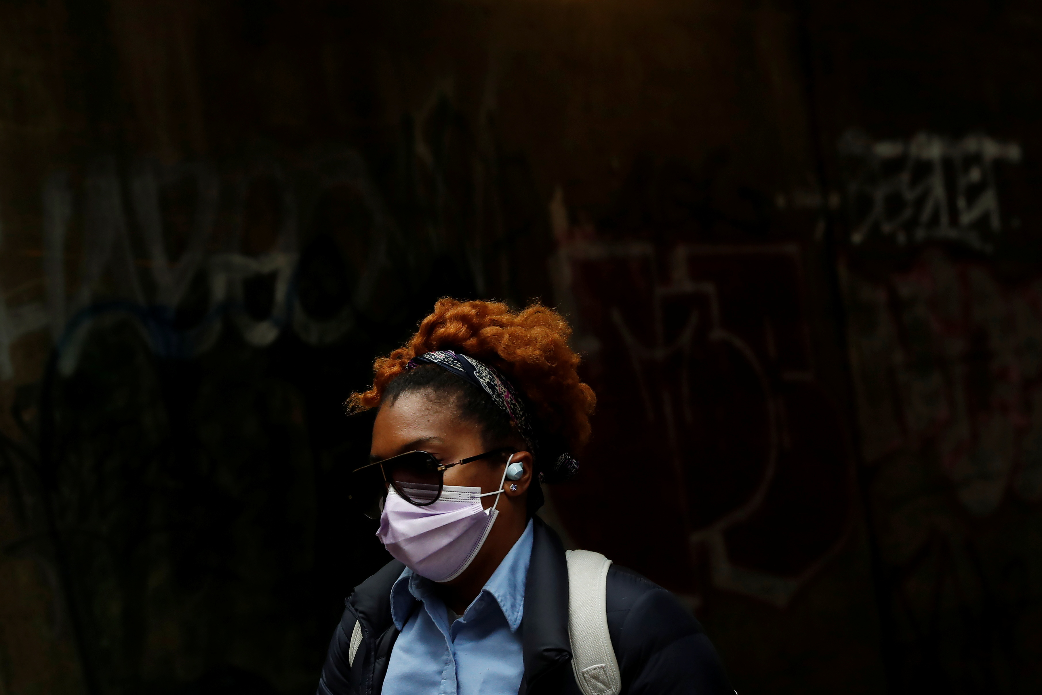 A woman wearing a protective mask walks under the subway in the Brownsville section of the Brooklyn borough of New York City, U.S., May 3, 2021. REUTERS/Shannon Stapleton