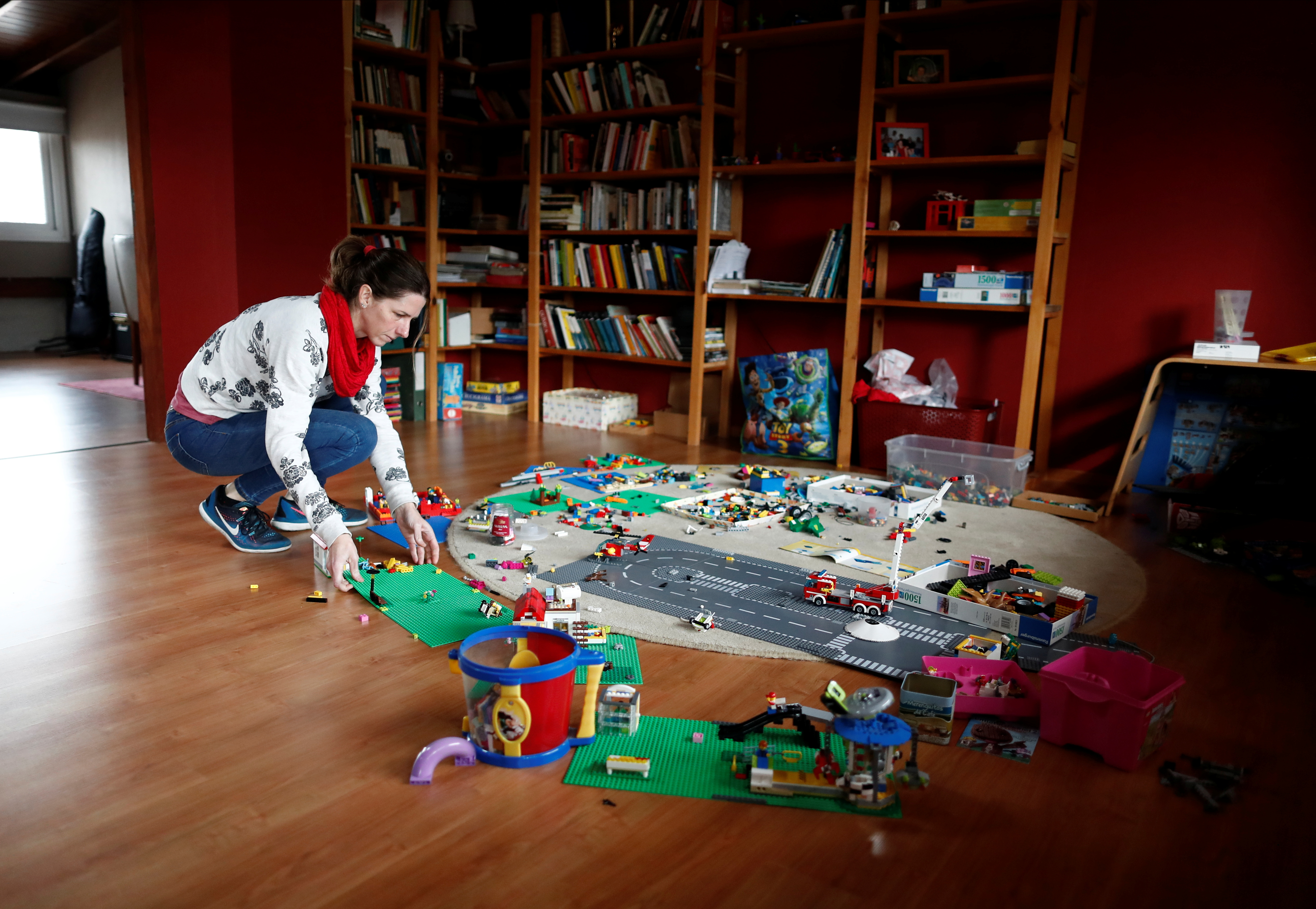 Barbara Temperley, 42, picks up her children's toys during a break from her home office, in Buenos Aires, Argentina September 6, 2021.  Latin America's mothers are lagging behind in the pandemic of economic recovery, returning to the labor force more slowly than men, in a trend that experts say could set back female labor force participation for a decade across the region. Picture taken September 6, 2021. REUTERS/Agustin Marcarian