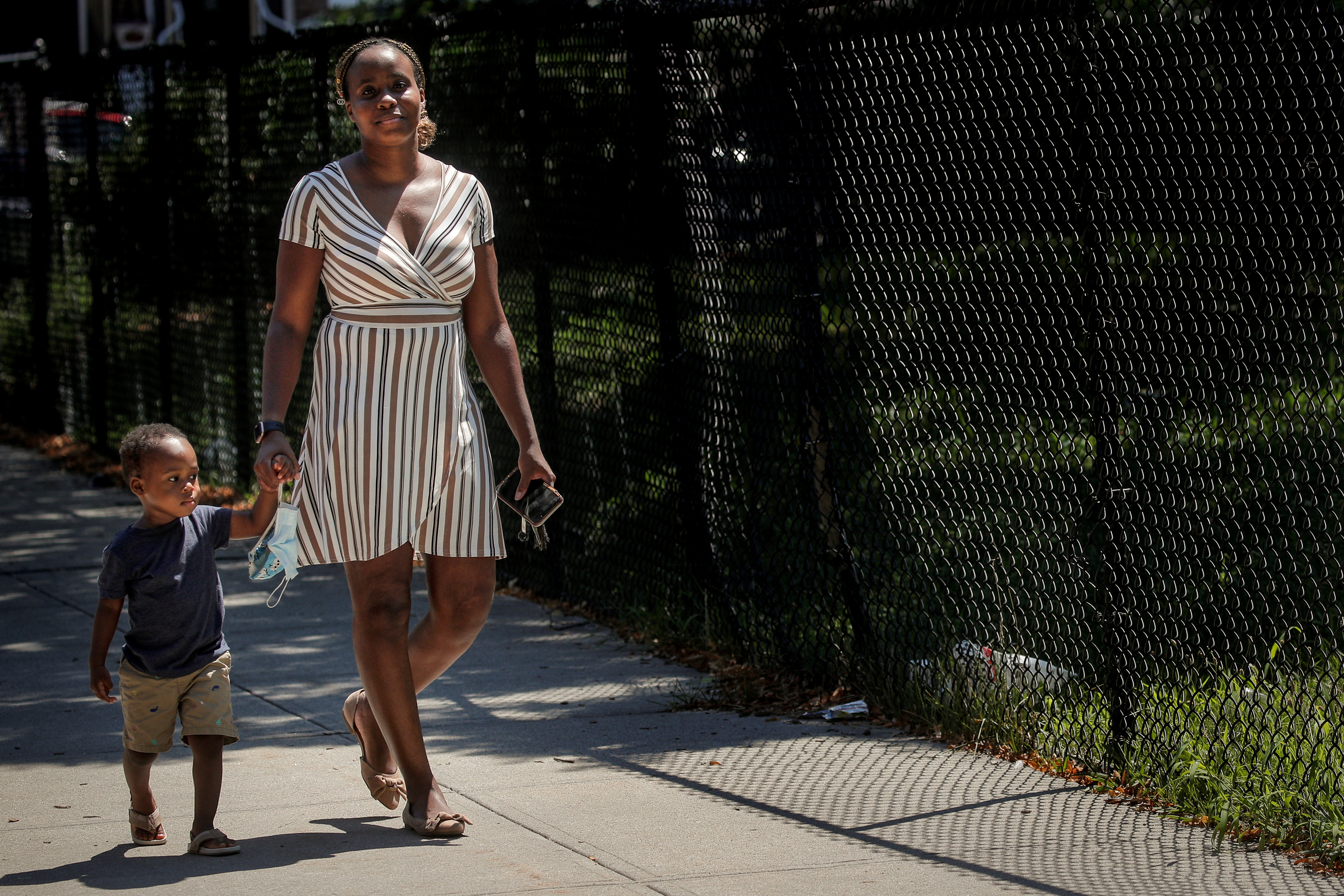 Chantel Springer walks with her son Jasiah in the Brooklyn borough of New York, U.S., July 29, 2020.  Picture taken July 29, 2020.  REUTERS/Brendan McDermid/File Photo