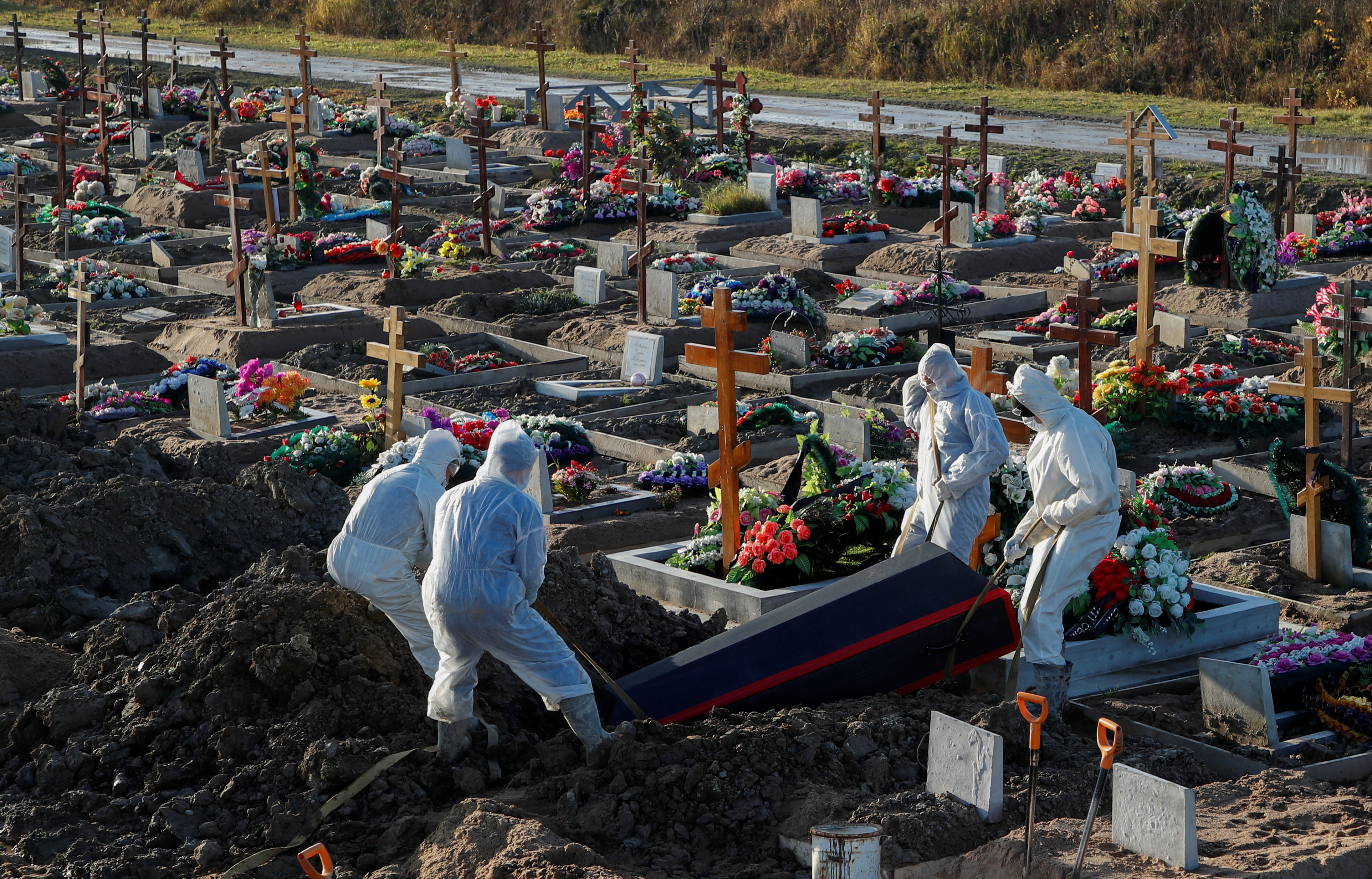 Grave diggers wearing personal protective equipment (PPE) lower a coffin while burying a person in the special purpose section of a graveyard for the coronavirus disease (COVID-19) victims on the outskirts of Saint Petersburg, Russia November 6, 2020. REUTERS/Anton Vaganov