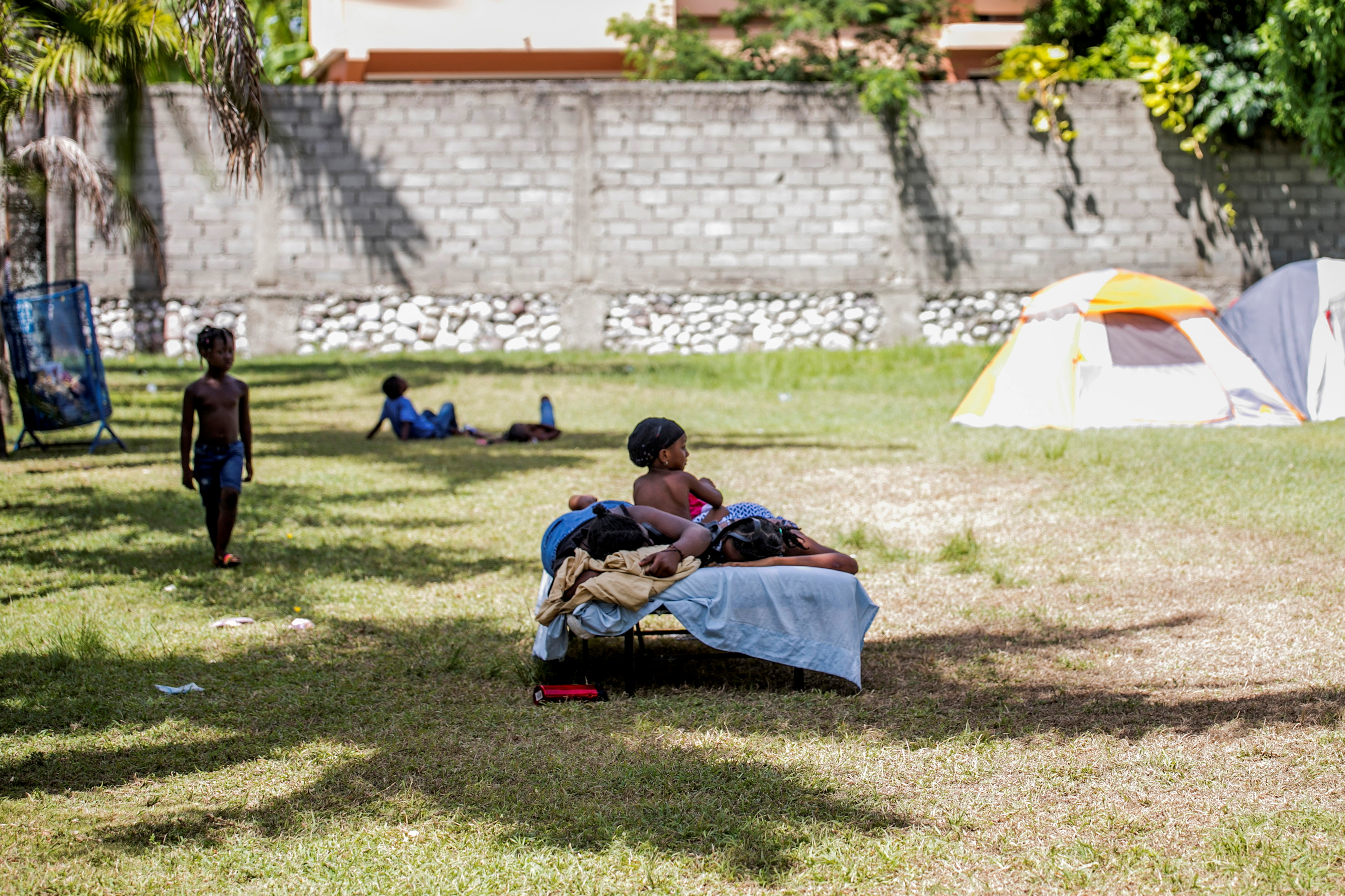 People stay in the shade at an encampment set up on a soccer field after Saturday's 7.2 magnitude quake, in Les Cayes, Haiti August 16, 2021. REUTERS/Ralph Tedy Erol