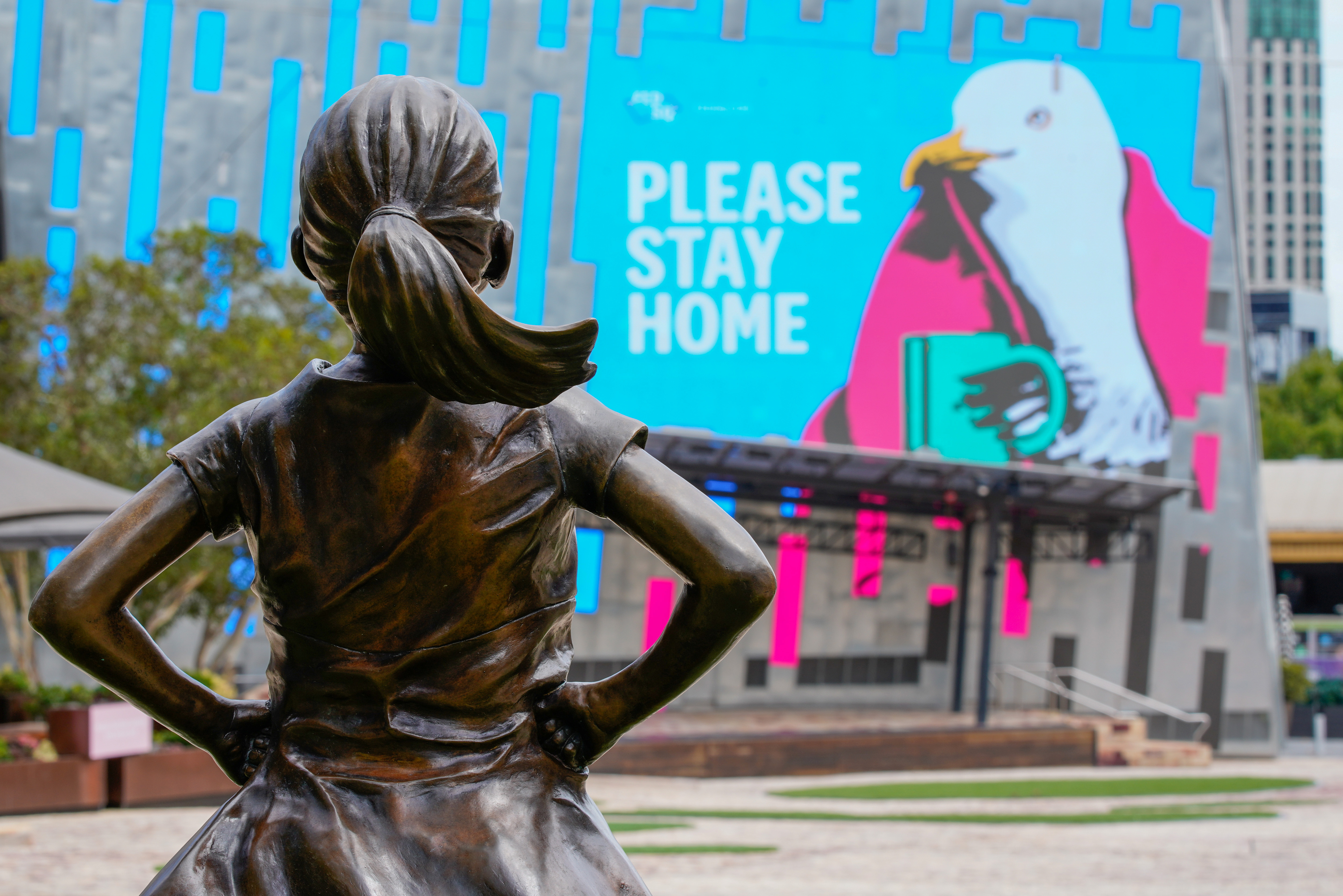 """The Fearless Girl Statue looks at a """"Please Stay Home"""" sign in an empty Federation Square on the first day of a five-day lockdown implemented in the state of Victoria in response to the coronavirus disease (COVID-19) outbreak in Melbourne, Australia, February 13, 2021.  REUTERS/Sandra Sanders"""