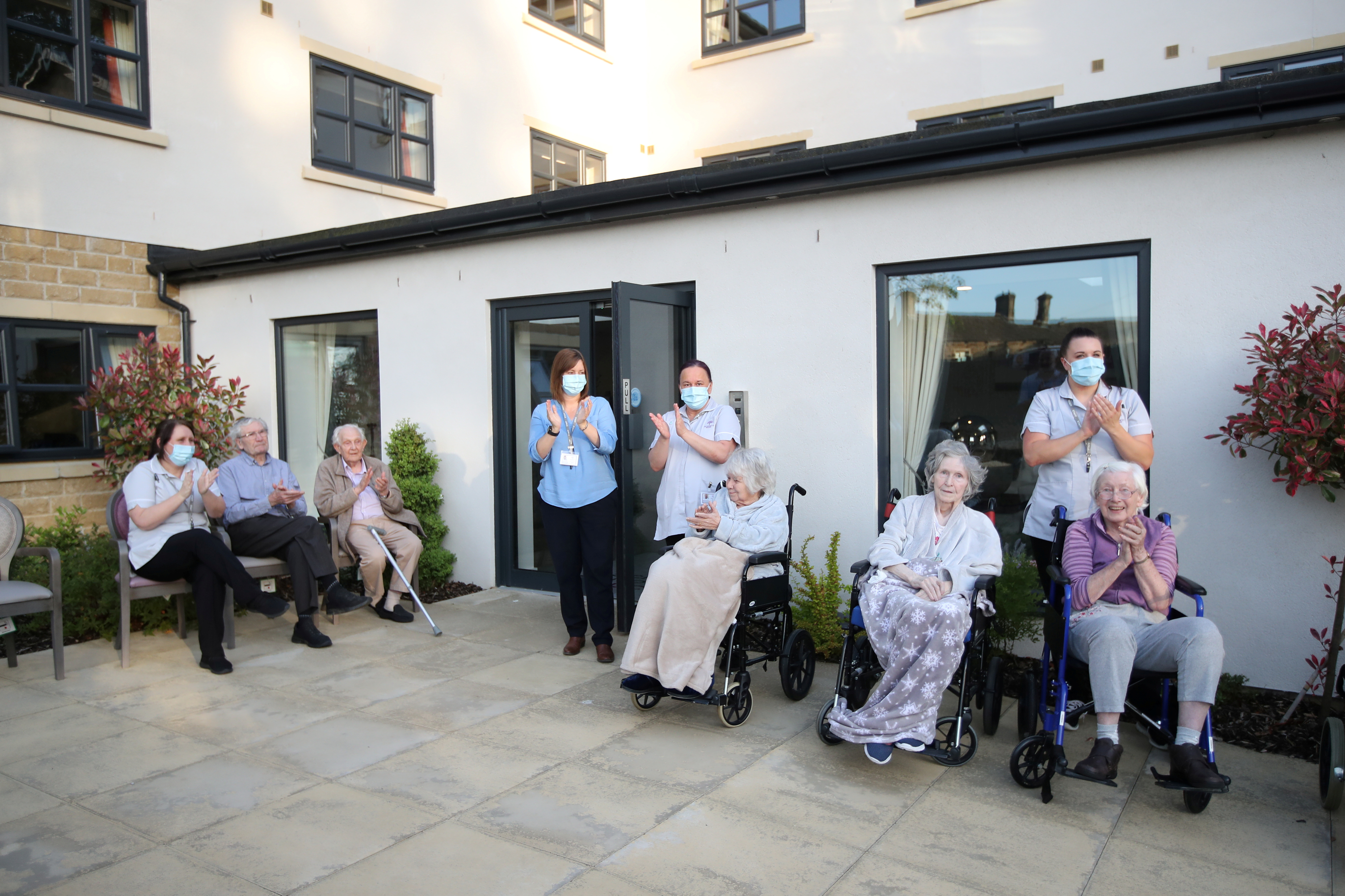 Care workers and residents of the Scisset Mount Care Home react during the last day of the Clap for our Carers campaign in support of the NHS, following the outbreak of the coronavirus disease (COVID-19), Huddersfield, Britain, May 28, 2020. REUTERS/Molly Darlington/File Photo