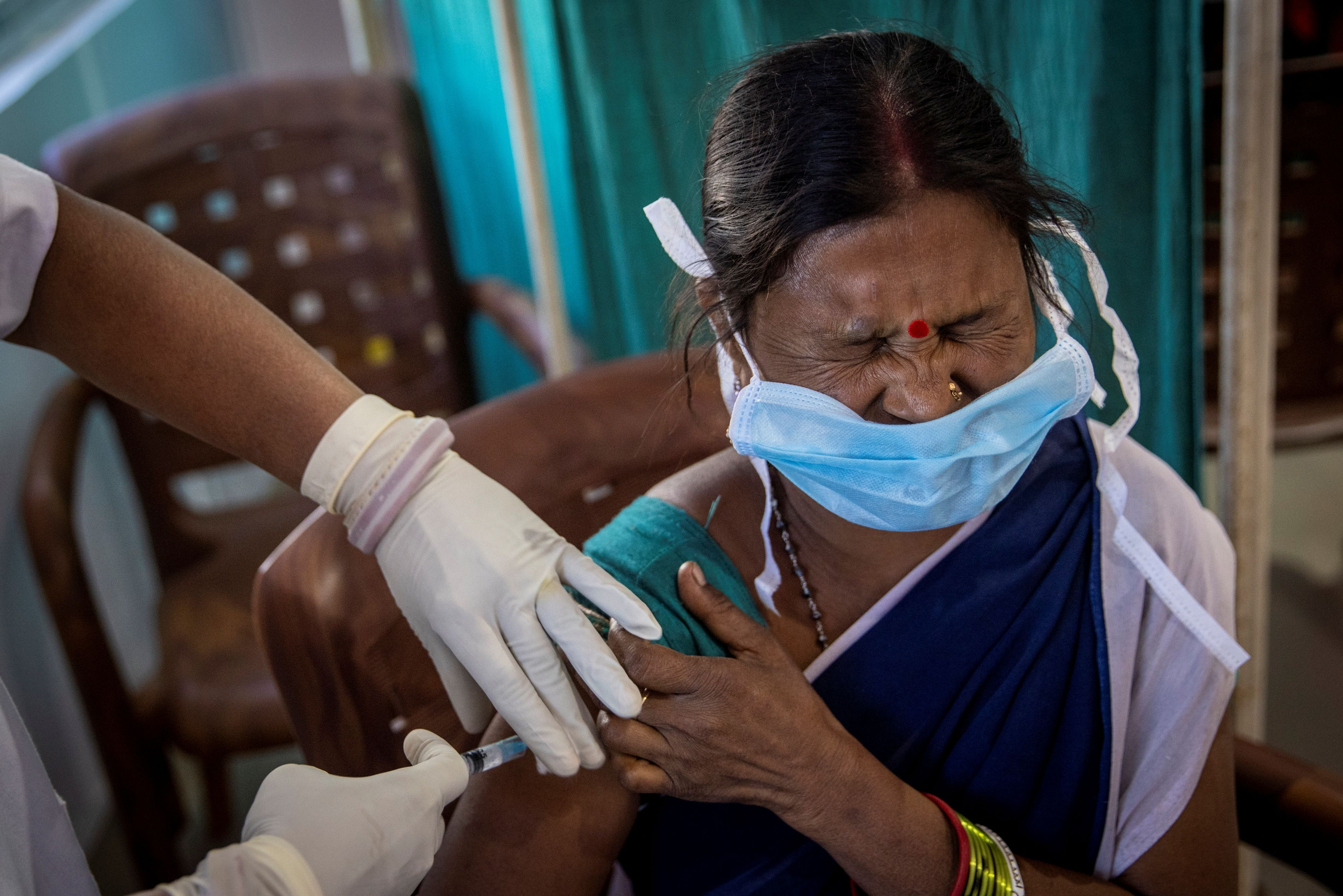 A healthcare worker reacts as she receives a dose of COVISHIELD, a COVID-19 vaccine manufactured by Serum Institute of India, during one of the world's largest COVID-19 vaccination campaigns at Mathalput Community Health Centre in Koraput district of the eastern state of Odisha, India, January 16, 2021. REUTERS/Danish Siddiqui