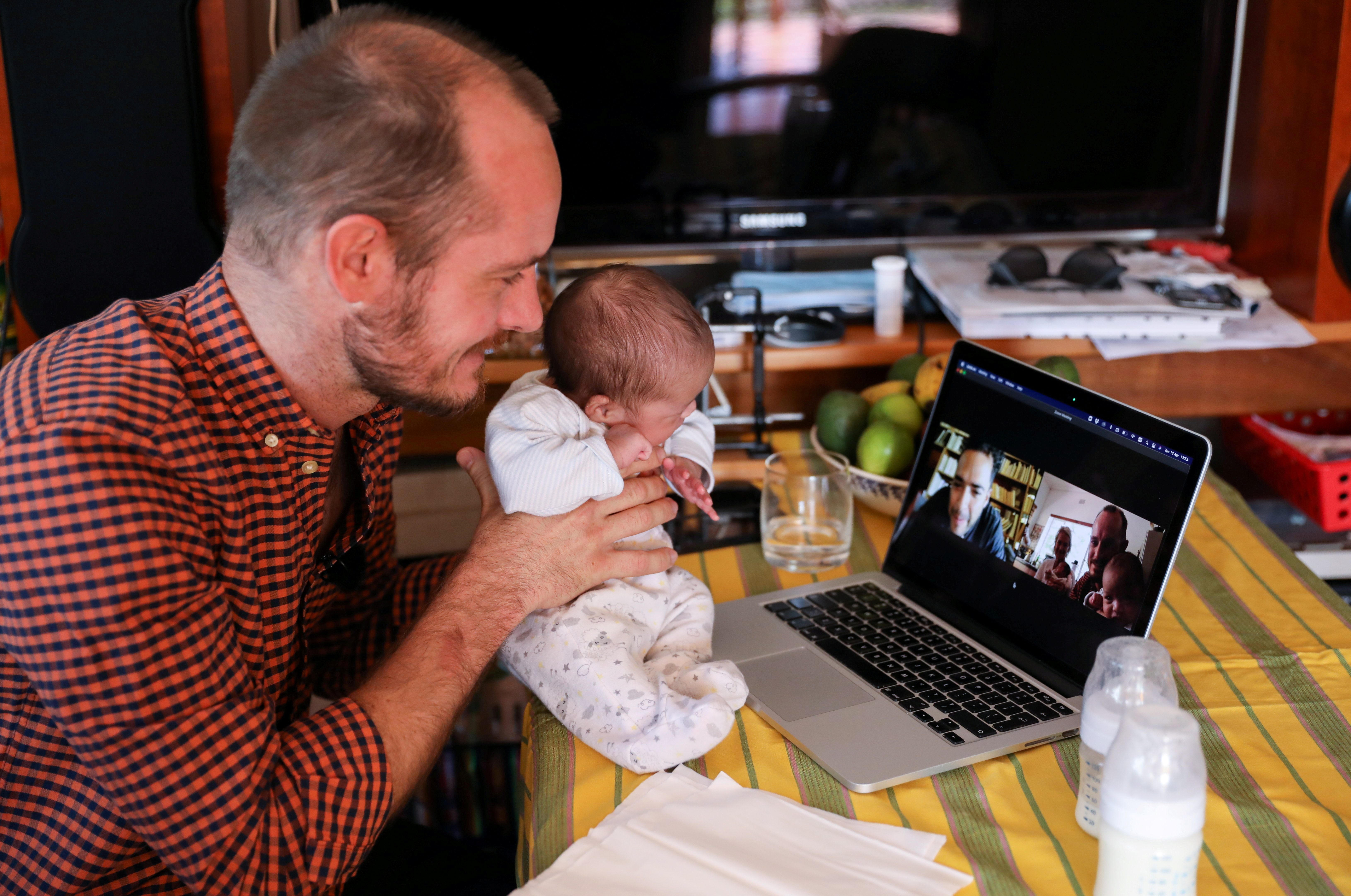 Namibian citizen Phillip Luhl holds one of his twin daughters as he speaks to his Mexican husband Guillermo Delgado via Zoom meeting in Johannesburg, South Africa, April 13, 2021. REUTERS/Siphiwe Sibeko