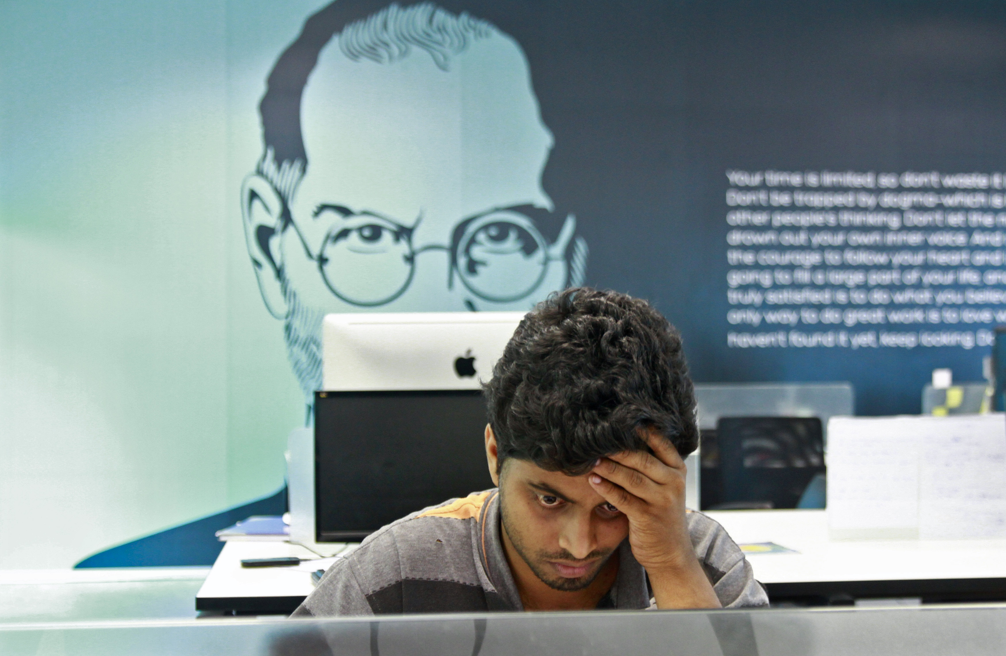 An employee works on a computer terminal against the backdrop of a picture of late Apple co-founder Steve Jobs at the Start-up Village in Kinfra High Tech Park in the southern Indian city of Kochi October 13, 2012. REUTERS/Sivaram V