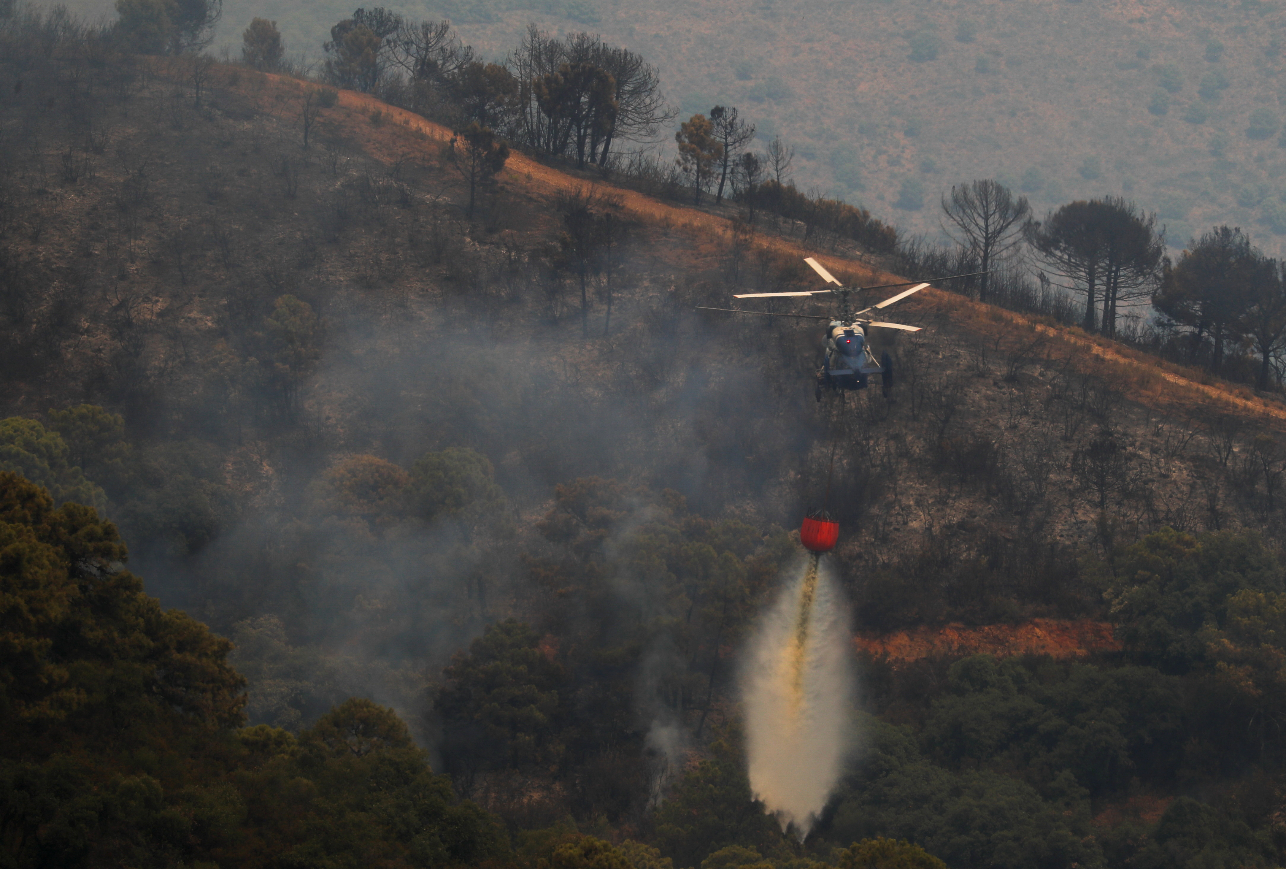 A helicopter makes a water drop over a wildfire on Sierra Bermeja mountain in Estepona, Spain, September 9, 2021. REUTERS/Jon Nazca