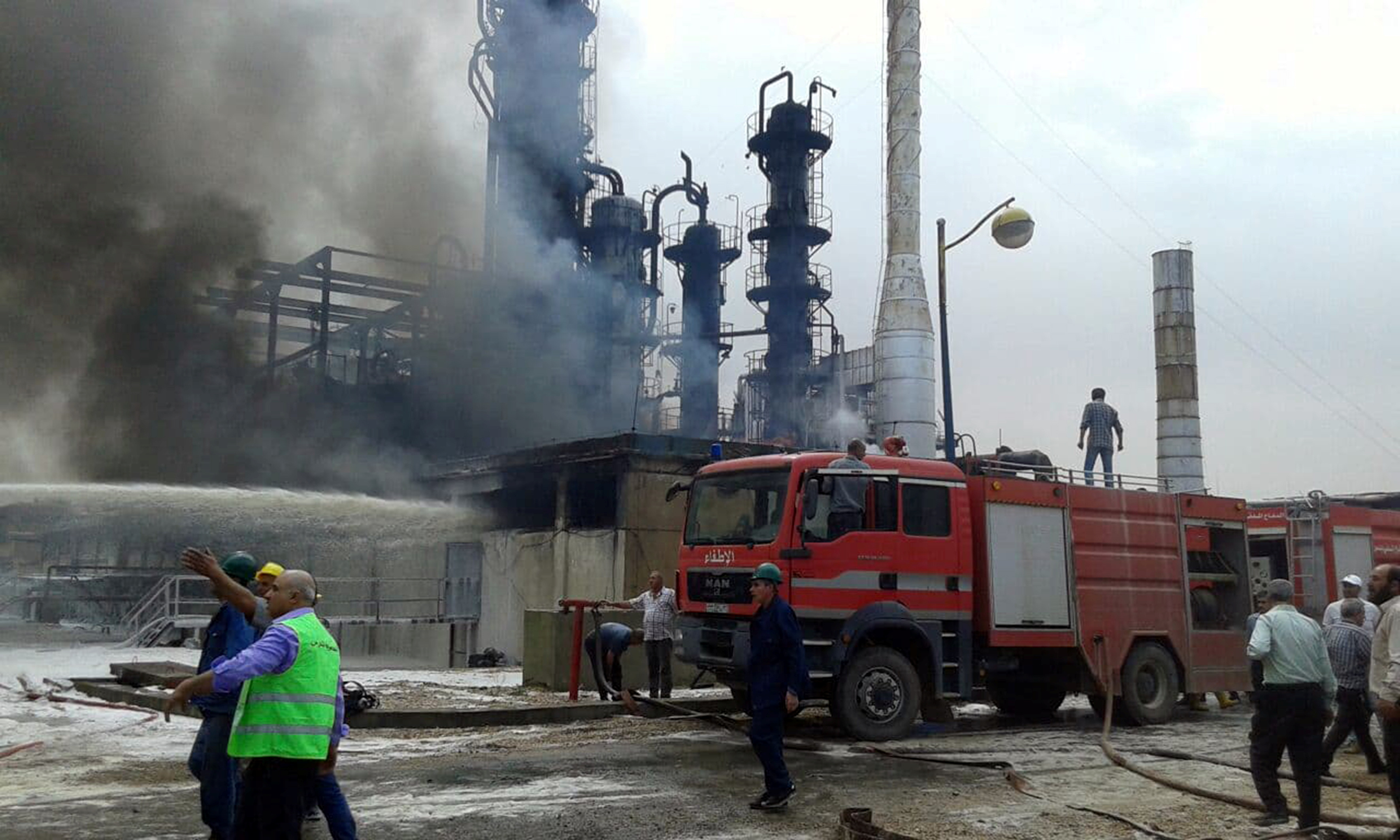Firefighters try to put out a fire in main Homs refinery, Syria, in this handout picture released on May 9, 2021. SANA/Handout via REUTERS