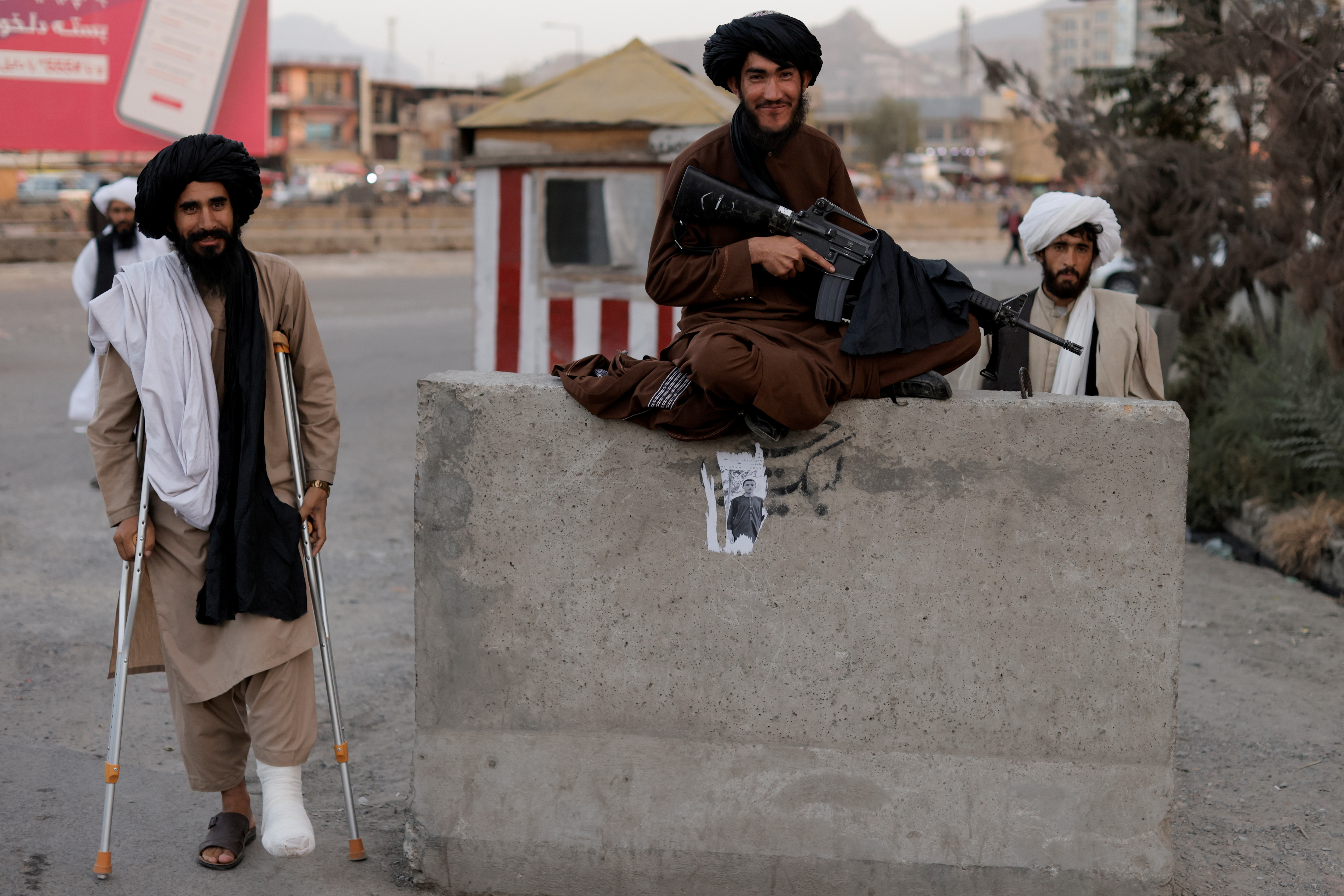 Taliban fighter Mira Jan Himmat, 30, and Rafiullah, 26, from Helmand province smile as they stand guard in a checkpoint in Kabul, Afghanistan October 5, 2021. REUTERS/Jorge Silva