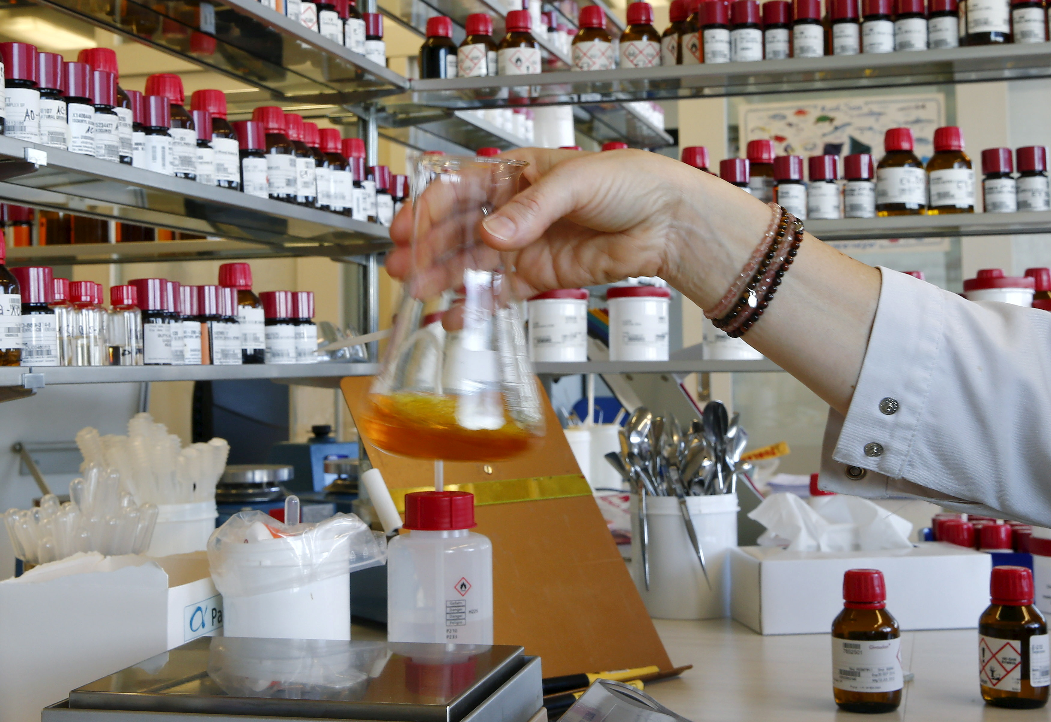 An employee mixes liquid fragrances in a bottle in a laboratory of Swiss flavours and fragrances maker Givaudan in the town of Duebendorf, Switzerland November 5, 2015.    REUTERS/Arnd Wiegmann/File Photo