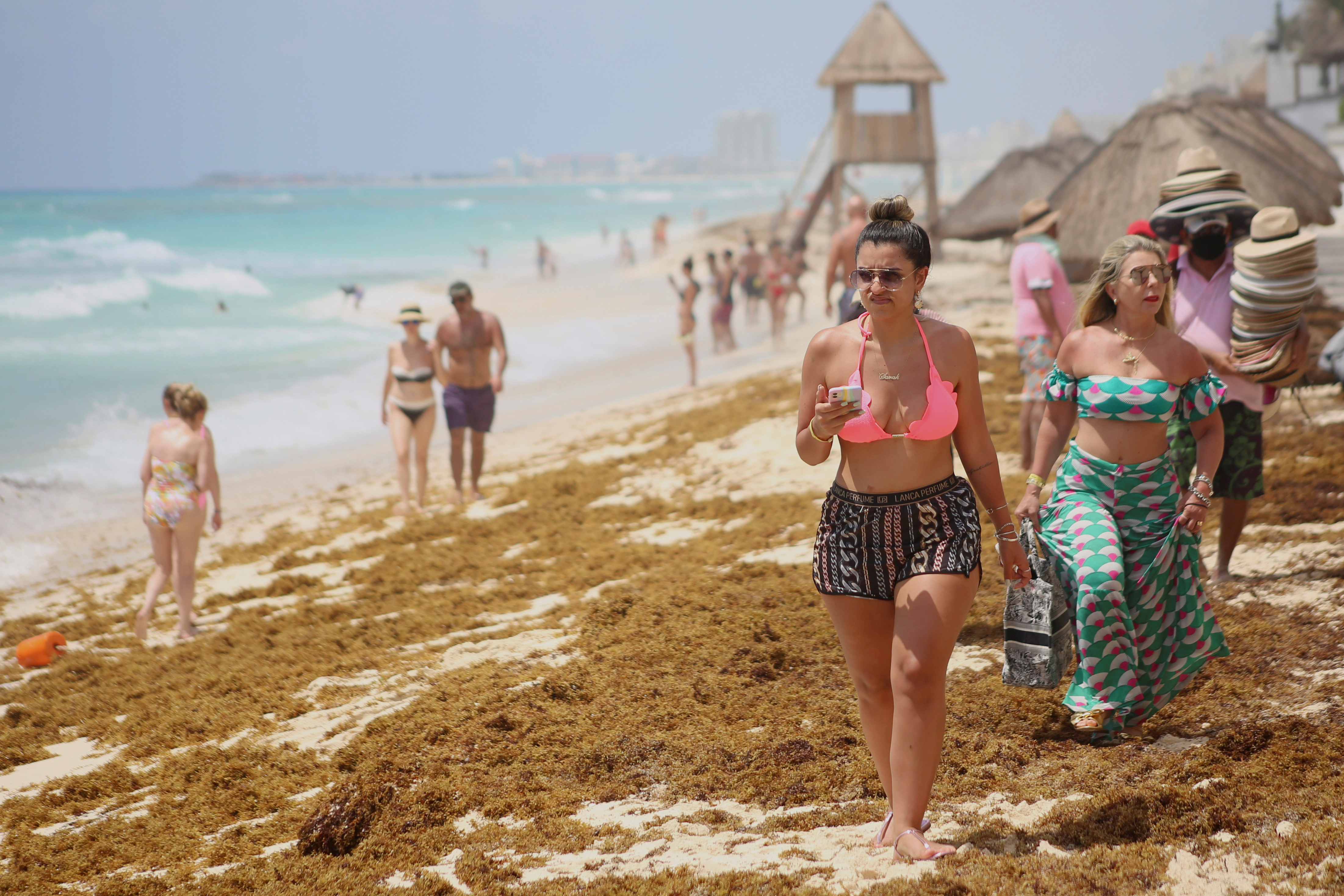Tourists walk over sand strewn with sargassum at Ballenas Beach in Cancun, Mexico July 23, 2021. Picture taken July 23, 2021. REUTERS/Paola Chiomante