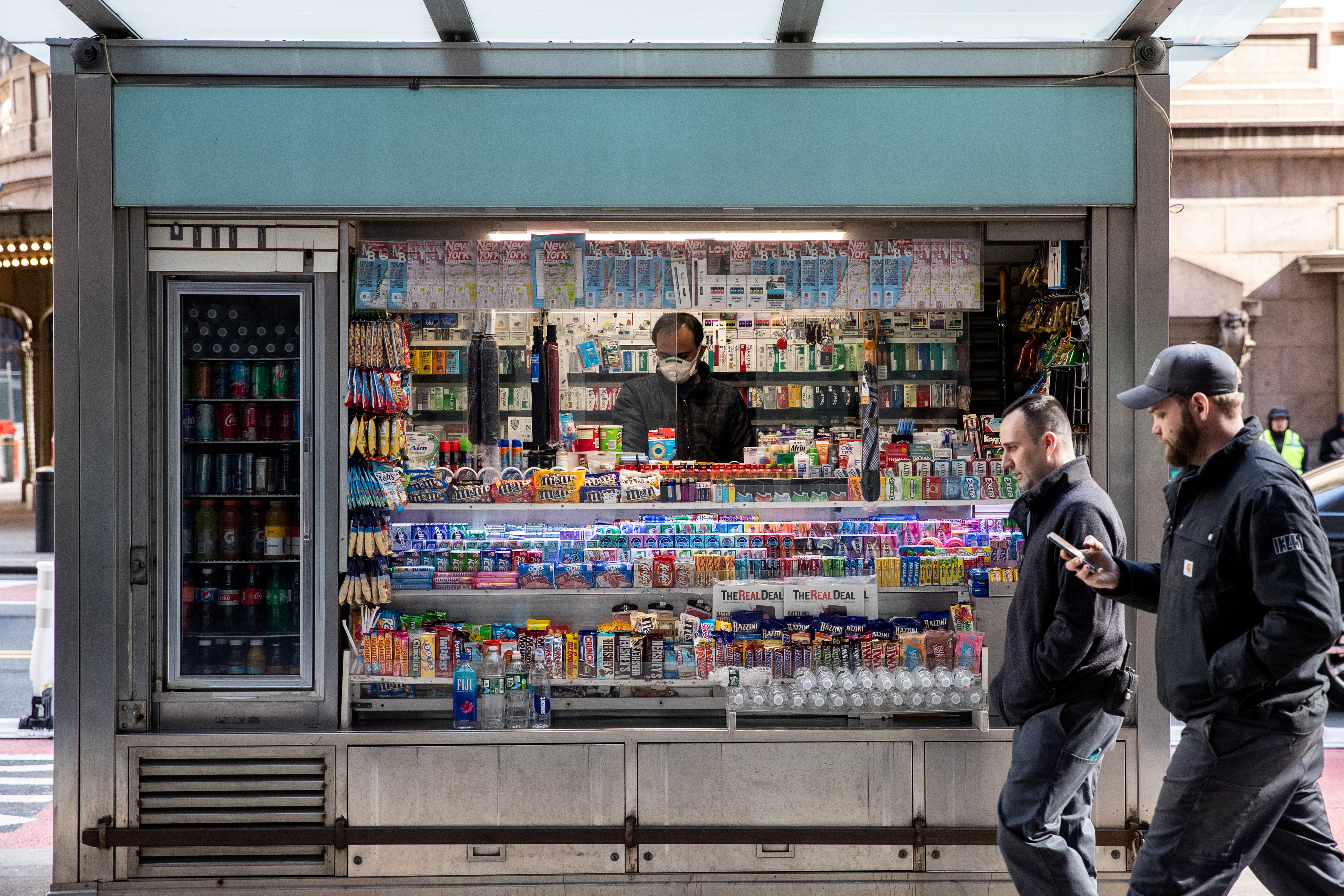 A man wearing a protective mask is seen at a newsstand following the outbreak of coronavirus disease (COVID-19), in New York City, U.S., March 16, 2020. REUTERS/Jeenah Moon/File Photo