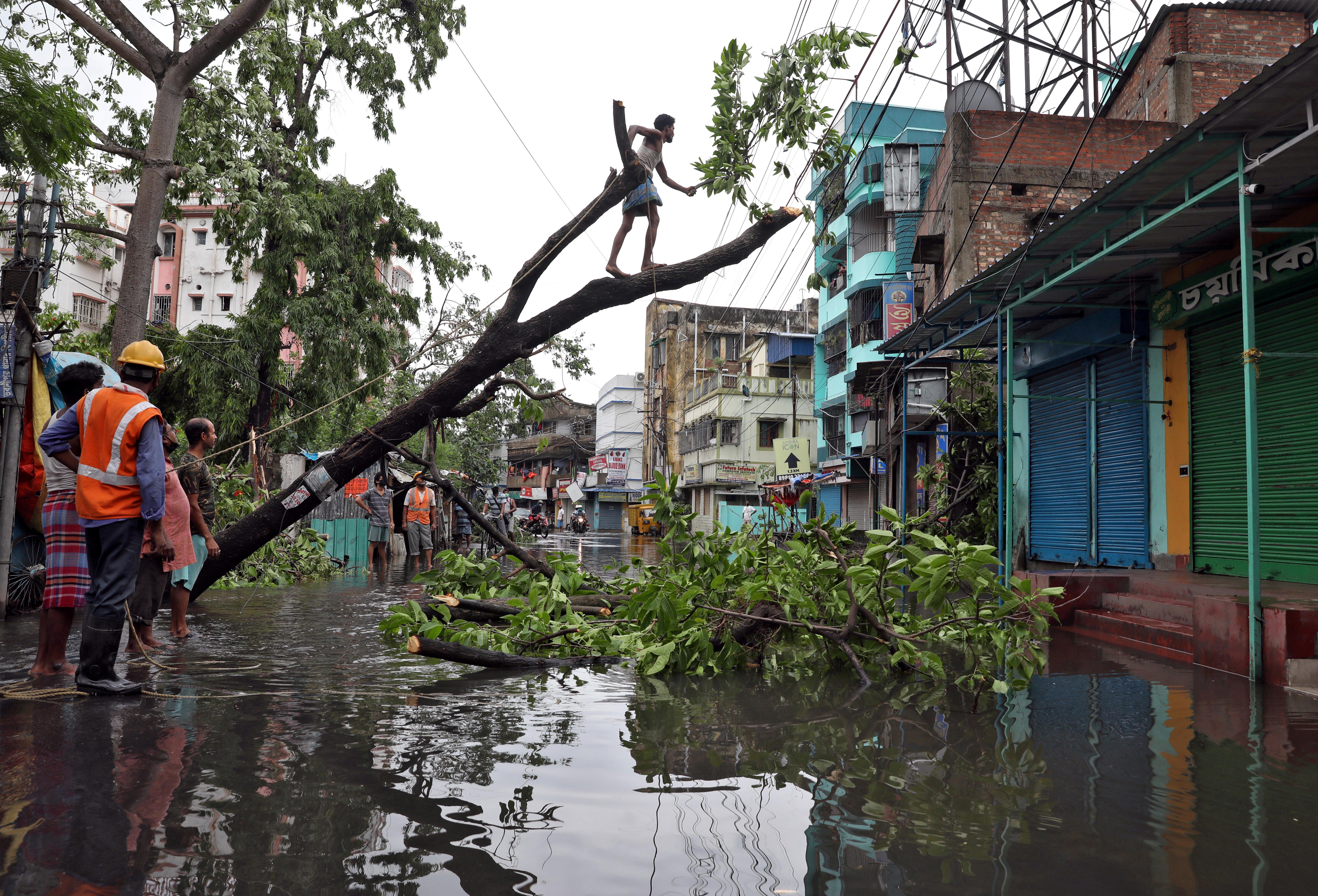 A man cuts branches of an uprooted tree after Cyclone Amphan made its landfall, in Kolkata, India, May 21, 2020. REUTERS/Rupak De Chowdhuri/Files
