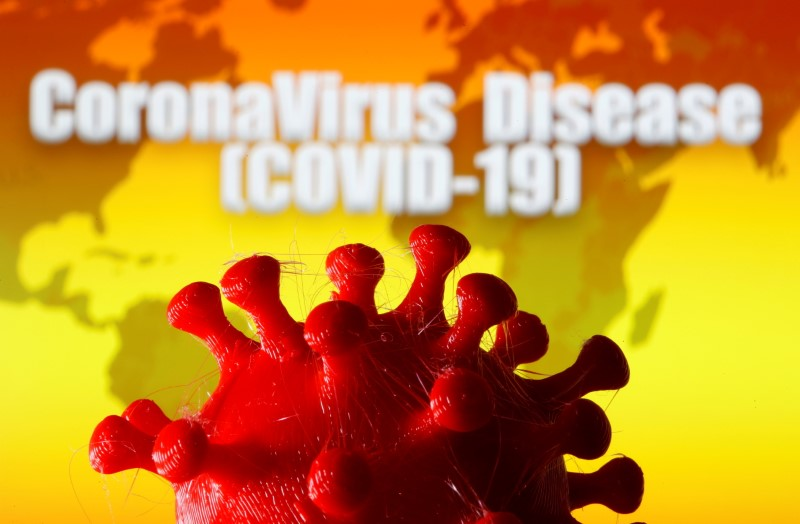 """A 3D-printed coronavirus model is seen in front of a world map and the words """"CoronaVirus Disease (Covid-19)"""" on display in this illustration taken March 25, 2020. REUTERS/Dado Ruvic/Illustration"""