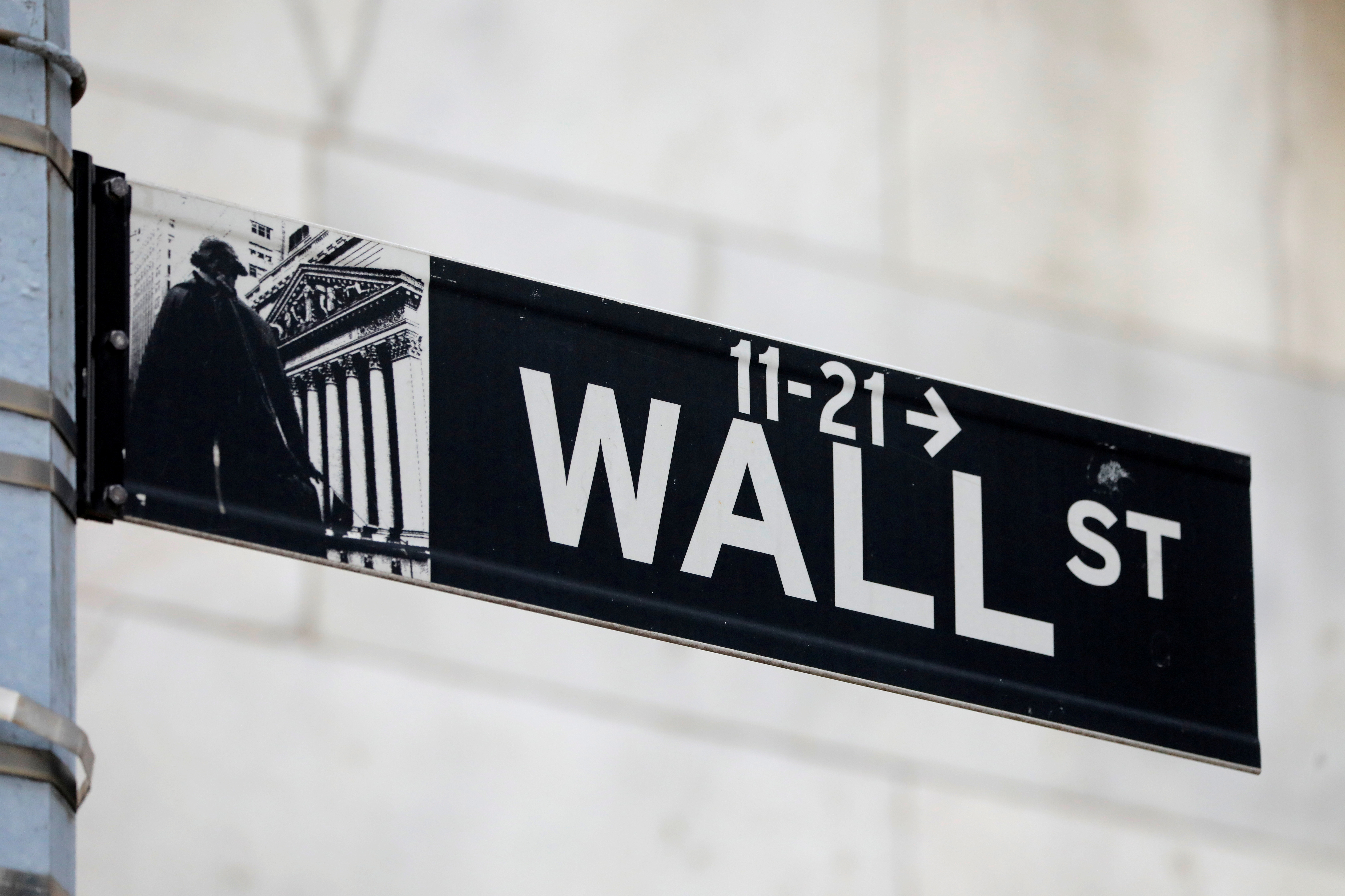 A street sign for Wall Street is seen outside of the New York Stock Exchange (NYSE) in New York City, New York, U.S., June 28, 2021. REUTERS/Andrew Kelly/File Photo