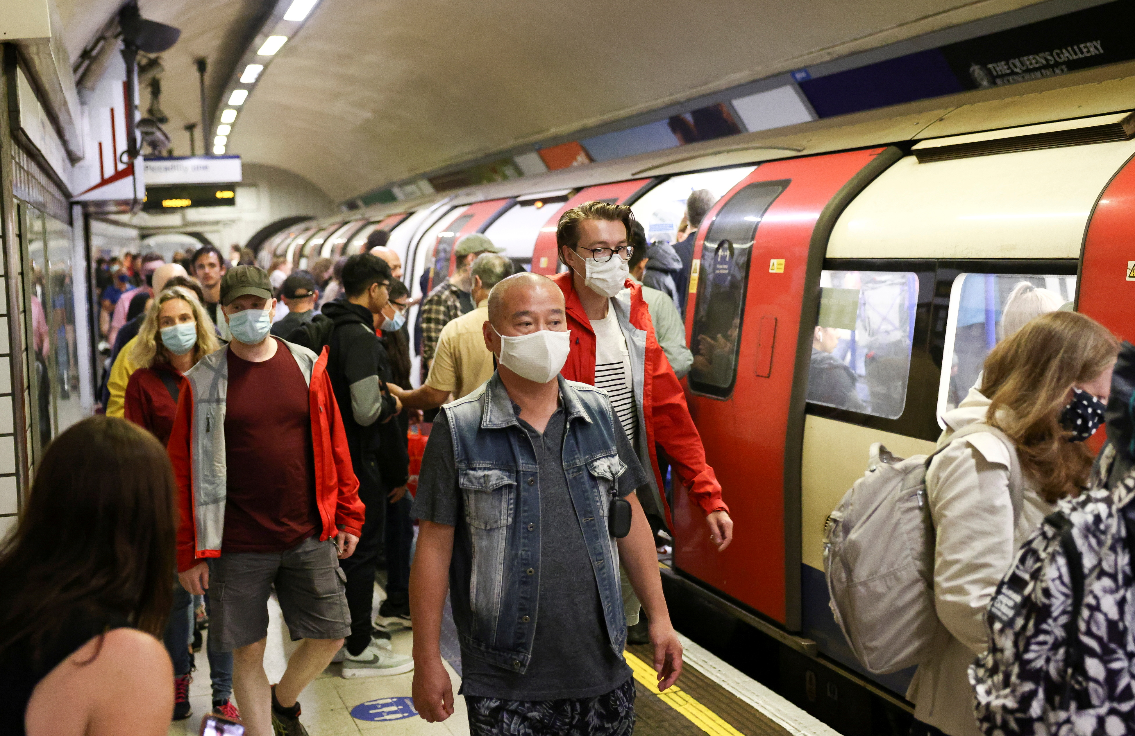 People wearing protective face masks walk along a platform on the London Underground, amid the coronavirus disease (COVID-19) outbreak, in London, Britain, July 25, 2021. REUTERS/Henry Nicholls/File Photo