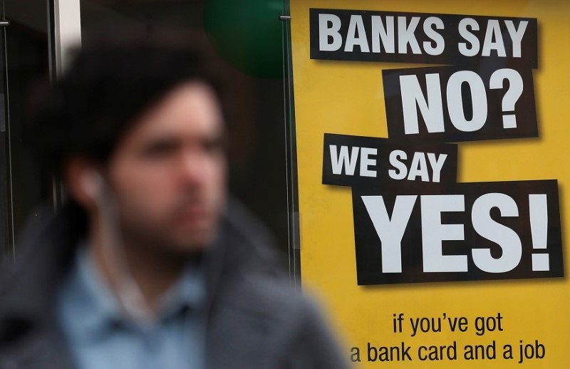 A pedestrian walks past a payday lending shop in London March 6, 2013. REUTERS/Suzanne Plunkett