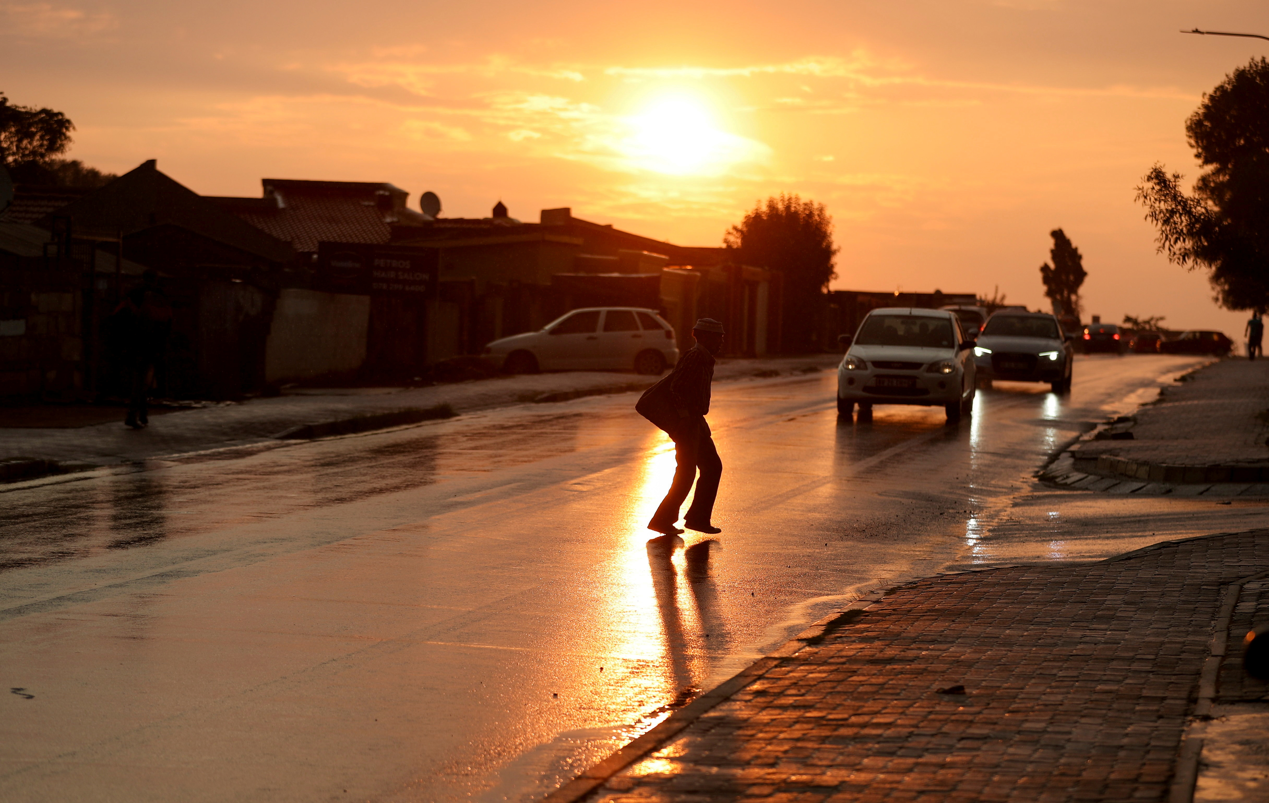 A person crosses the street during sunset, amid the coronavirus disease (COVID-19) outbreak, in Soweto, South Africa, April 1, 2021. REUTERS/Siphiwe Sibeko