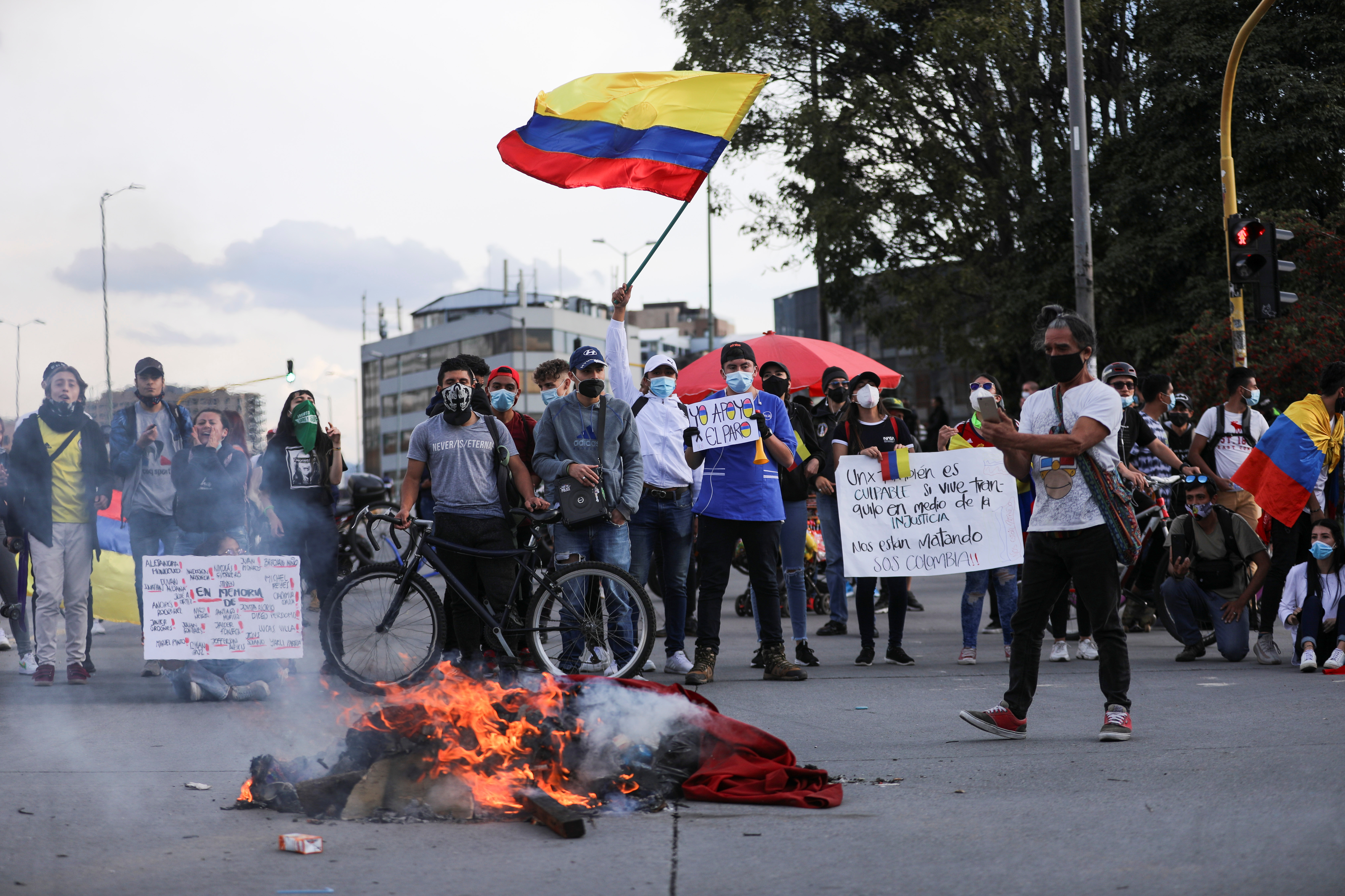Demonstrators stand near burning objects as they take part in a protest demanding government action to tackle poverty, police violence and inequalities in the health and education systems, in Bogota, Colombia May 6, 2021. REUTERS/Luisa Gonzalez