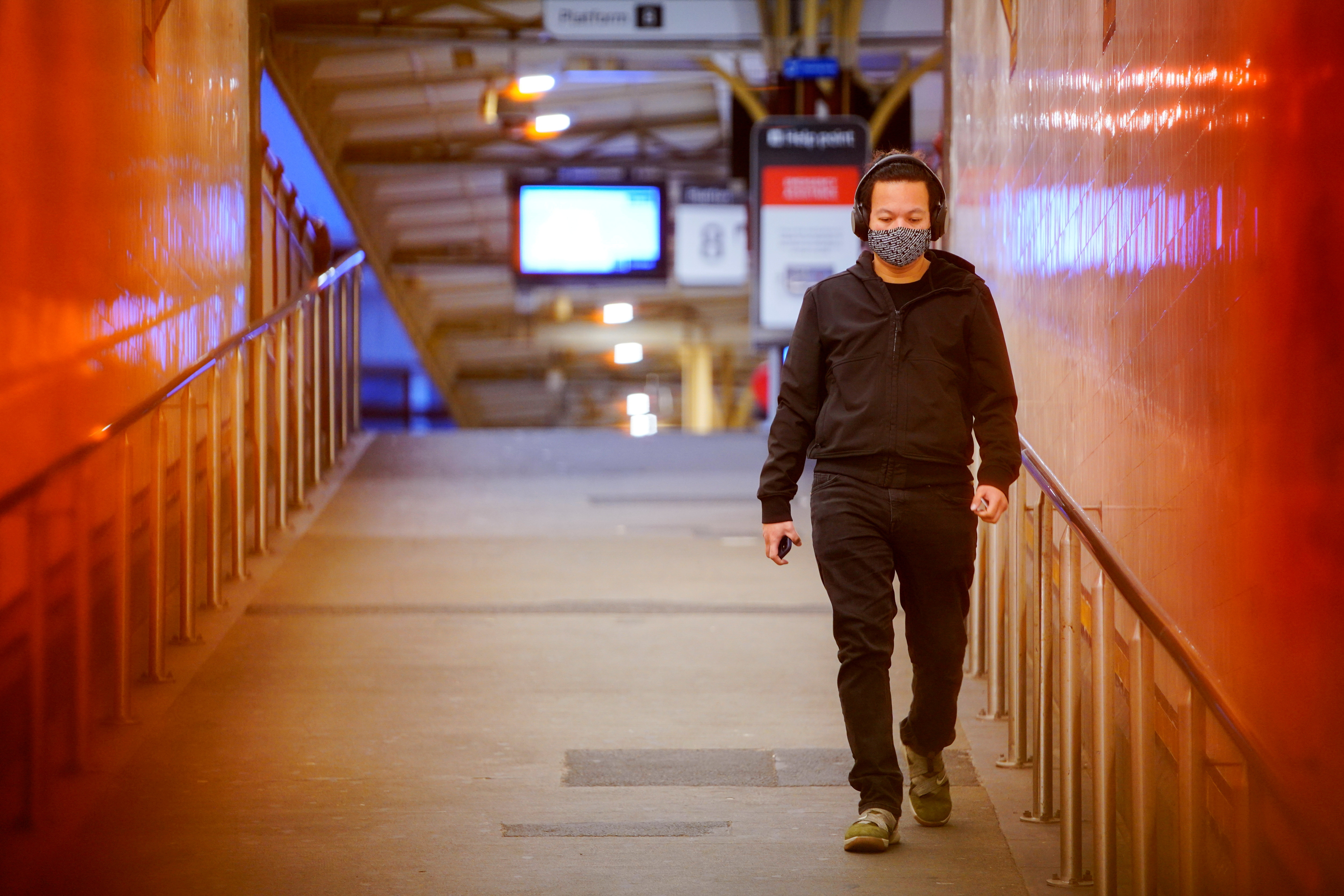 A lone passenger wearing a protective face mask walks from a deserted train platform at Flinders Street during morning commute hours on the first day of a lockdown as the state of Victoria looks to curb the spread of a coronavirus disease (COVID-19) outbreak in Melbourne, Australia, July 16, 2021.  REUTERS/Sandra Sanders/File Photo/File Photo
