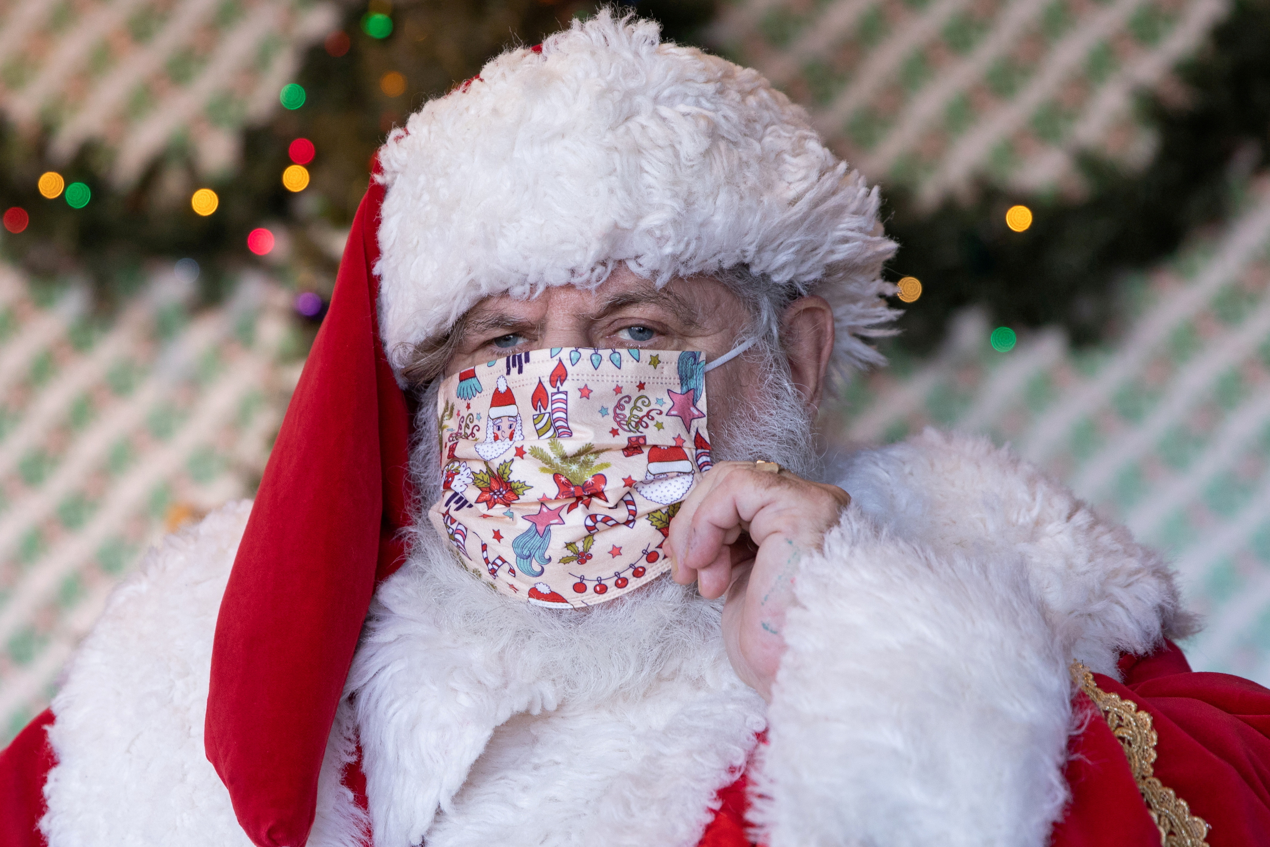 Dana Friedman, a trial lawyer who has spent 6 months of each year growing out his beard for his annual appearances as Santa Claus since 2001, adjusts his mask before greeting a child at the Bay Terrace Shopping Center in Queens as the global outbreak of the coronavirus disease (COVID-19) continues, in New York City, U.S., December 6, 2020. REUTERS/Caitlin Ochs/File Photo