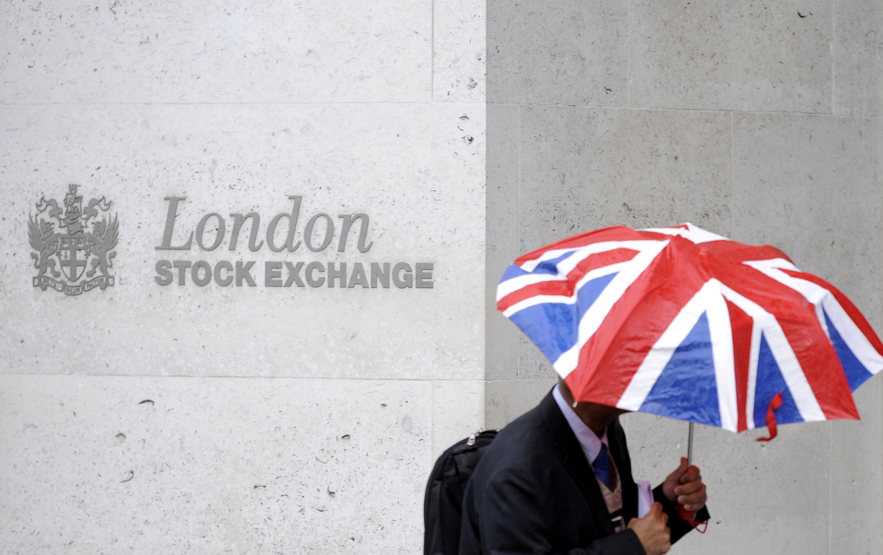 A worker shelters from the rain under a Union Flag umbrella as he passes the London Stock Exchange in London, Britain, October 1, 2008.  REUTERS/Toby Melville
