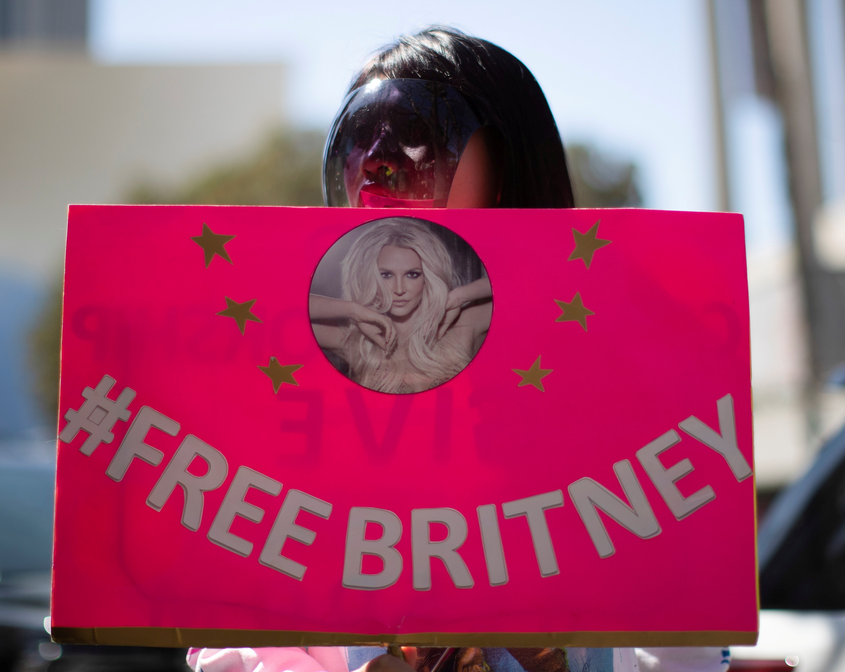 A supporter wearing a personal protective face shield holds a sign while rallying for pop star Britney Spears during a conservatorship case hearing at Stanley Mosk Courthouse in Los Angeles, California, U.S., March 17, 2021.  REUTERS/Mario Anzuoni
